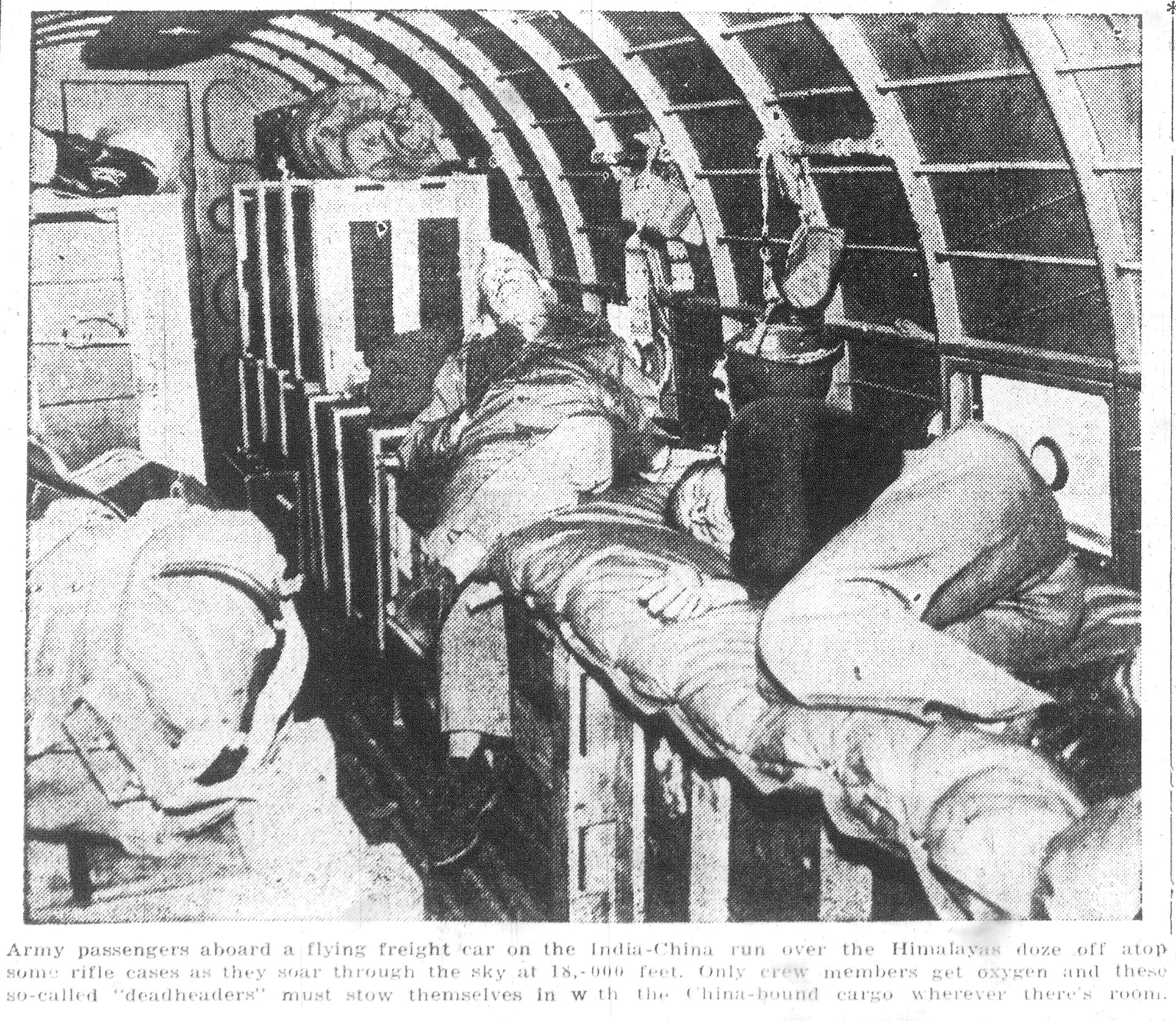Army passengers aboard a flying freight car on the India-China run over the Himalayas doze off atop some