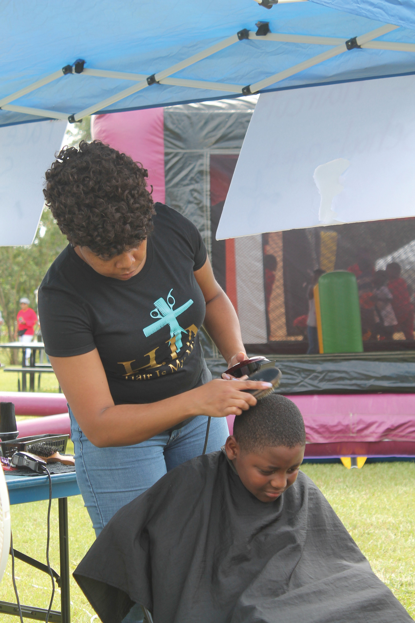 "Jonathan Livingston, 9, gets a free back-to-school haircut at the ""Changing the World One Community at a Time"" event held Saturday at Summerton's Wausaw Park. The event was sponsored by the Creating Memories Life Changing Corp. formed by David and Tanika Blanding to give children an alternative to life on the streets."