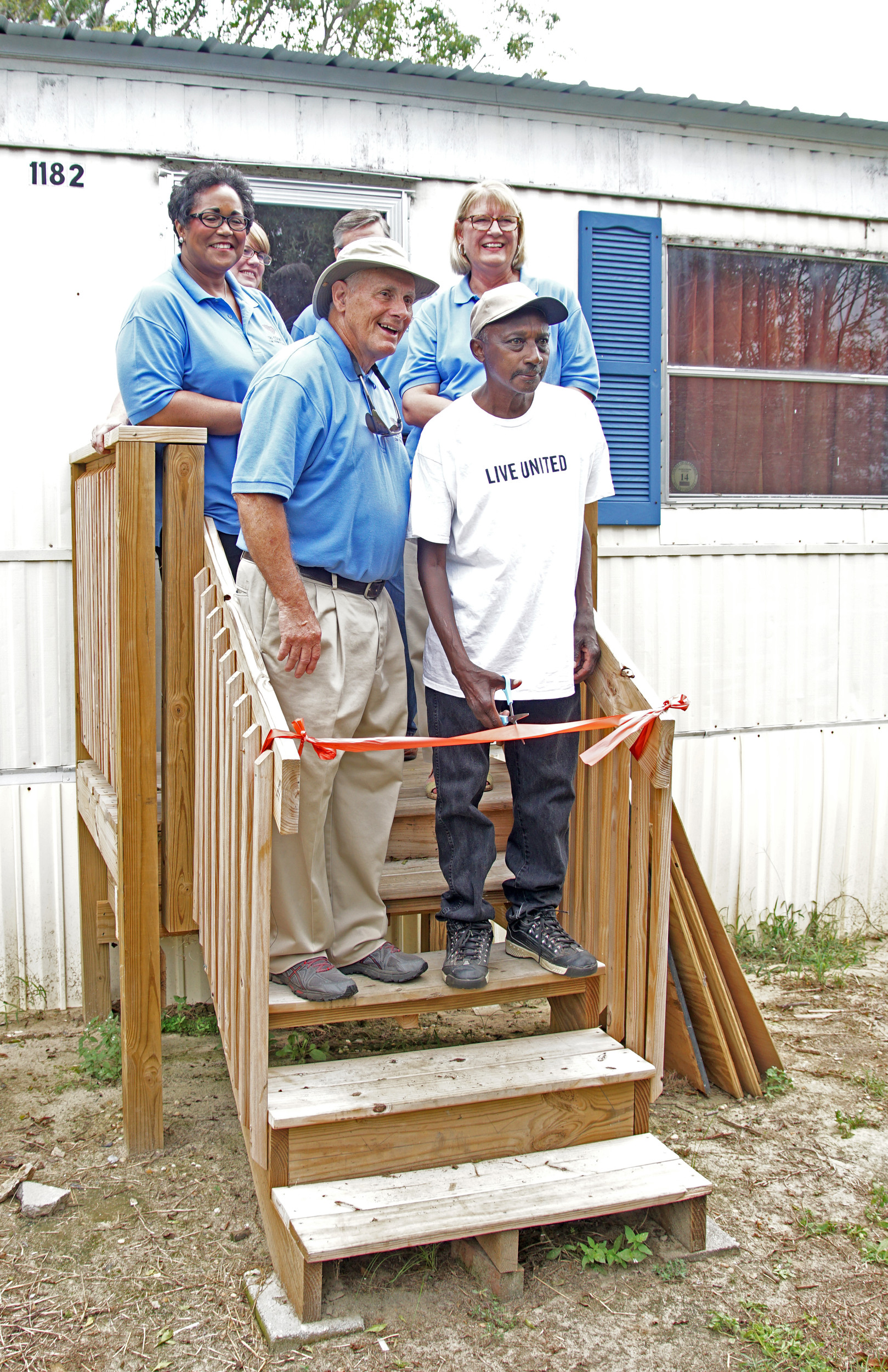 Curtis Billie and some of the volunteers who helped repair his home after it was damaged during the October 2015 flood cut a ribbon celebrating Billie's return to his home this past week near Pinewood.