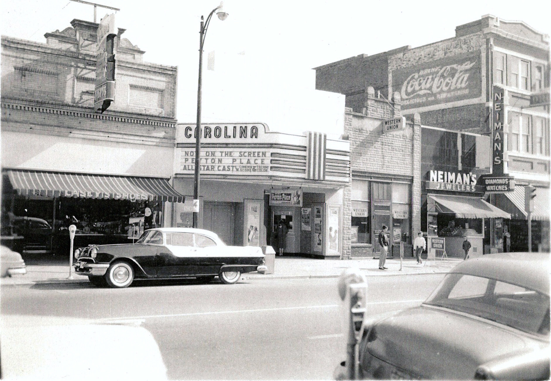 "The Carolina Theatre is shown on South Main Street in the late 1950s or early '60s. Note that the film ""Peyton Place,"" then being shown at the Carolina, was released in 1957. Ten years later, the theater was sold and closed by the purchaser, Winyah Bay Co."