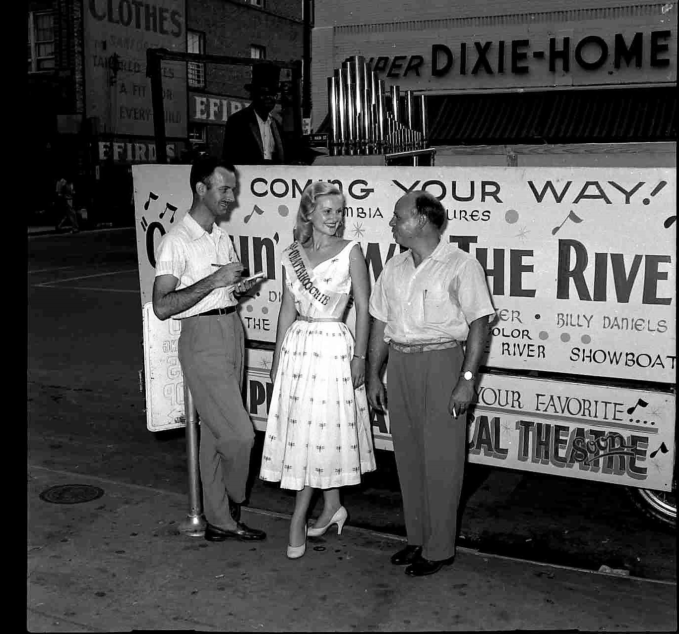 "Miss Chattahoochee and Professor Lindsay visit Sumter as advance publicity agents for ""Cruisin' Down the River,"" Columbia's Technicolor musical, which was shown at the Carolina Theatre. The brown-eyed blonde, Miss Doris Haglar, Miss Charlotte 1953, is being interviewed by Item reporter John Mitchell, left, as she and J. Lawrence Goldsmith, manager of the theater, discuss the film."