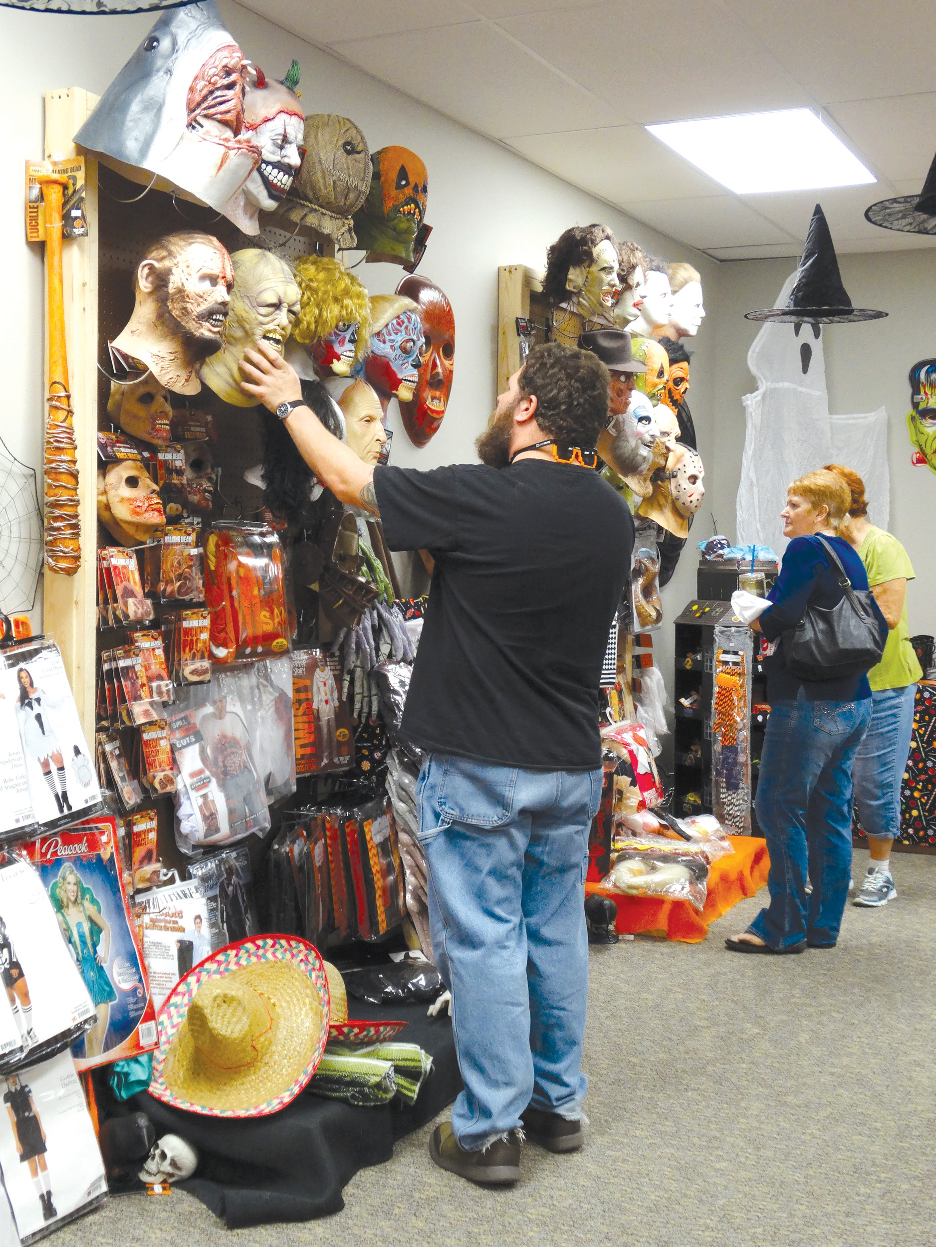 photos by MELANIE SMITH / THE SUMTER ITEM  Jeff Whisnant of Sumter checks out a mask at M and M's Lil Shop o' Horrors on West Liberty Street on Tuesday afternoon. He said he'd heard about the Halloween shop on Facebook and that his friends were also interested in visiting the new store. It will be open through the first week of November and offers costumes and fall decorations.