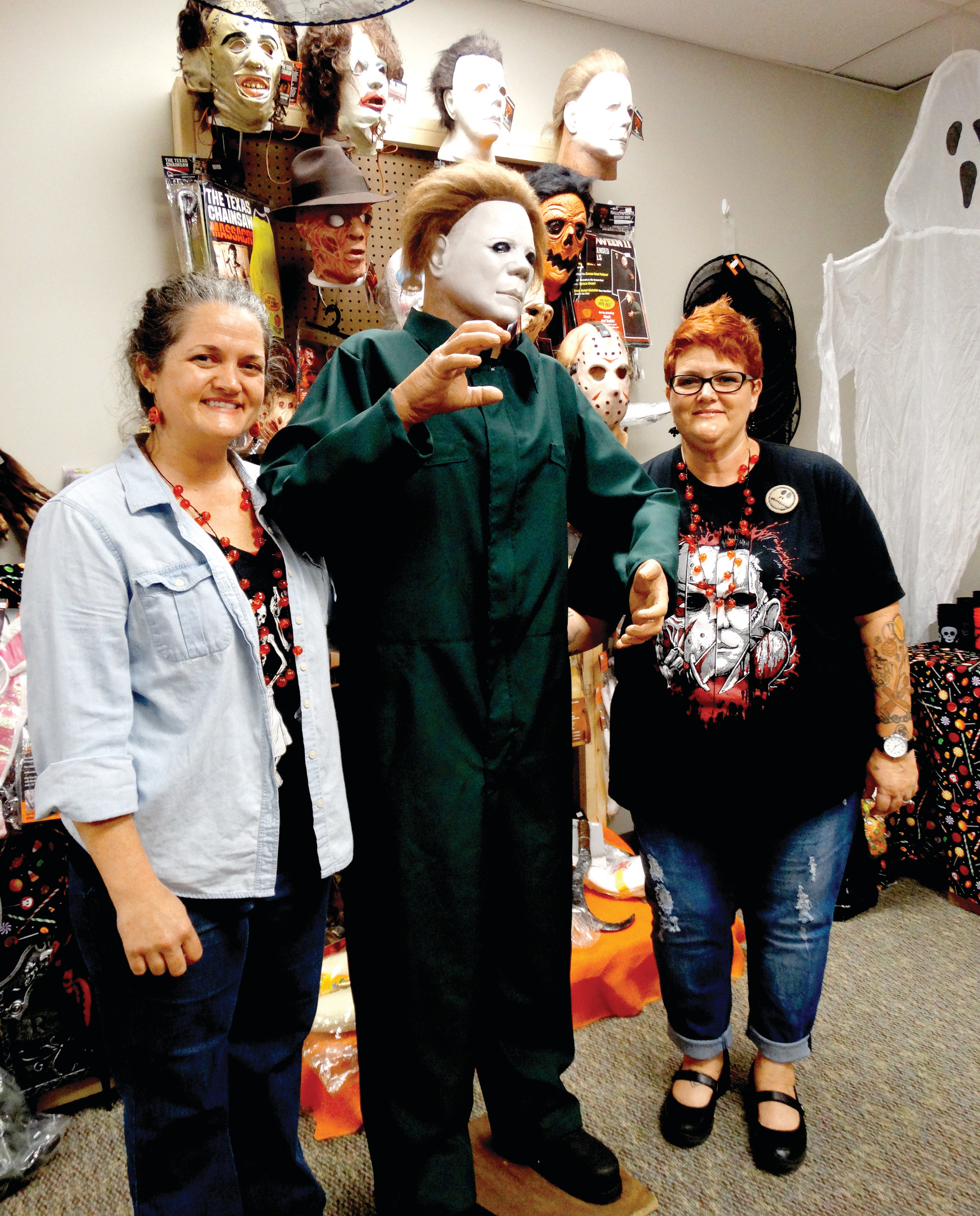 Melanie Lee, left, Michael Myers, center, and Miranda Johns, far right, pose for a picture on the day of the grand opening of M and M's Lil Shop O' Horrors on Tuesday. The shop, located on West Liberty Street, sells a variety of Halloween costumes and decorations as well as fall and Thanksgiving items.