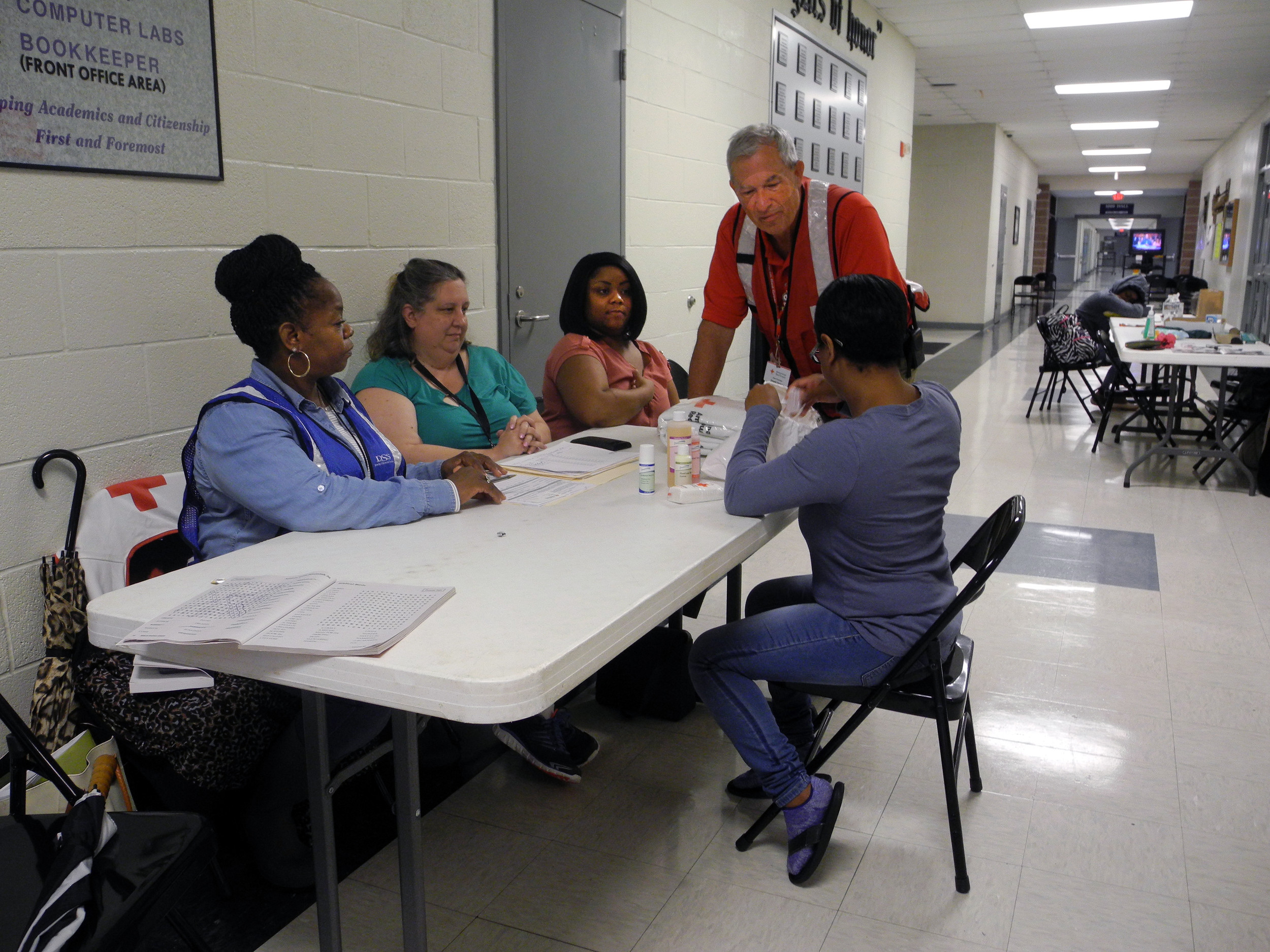 Sumter County Department of Social Services staff registered evacuees coming in to the Red Cross Shelter at Crestwood High School on Sunday night and Monday. Here a new arrival looks through the bag of toiletries provided by the Red Cross and presented to her by the shelter manager, Steve Shumake, standing. From left, the DSS staff are Janice Portee, Kristie Leahey and Shatola Allen.