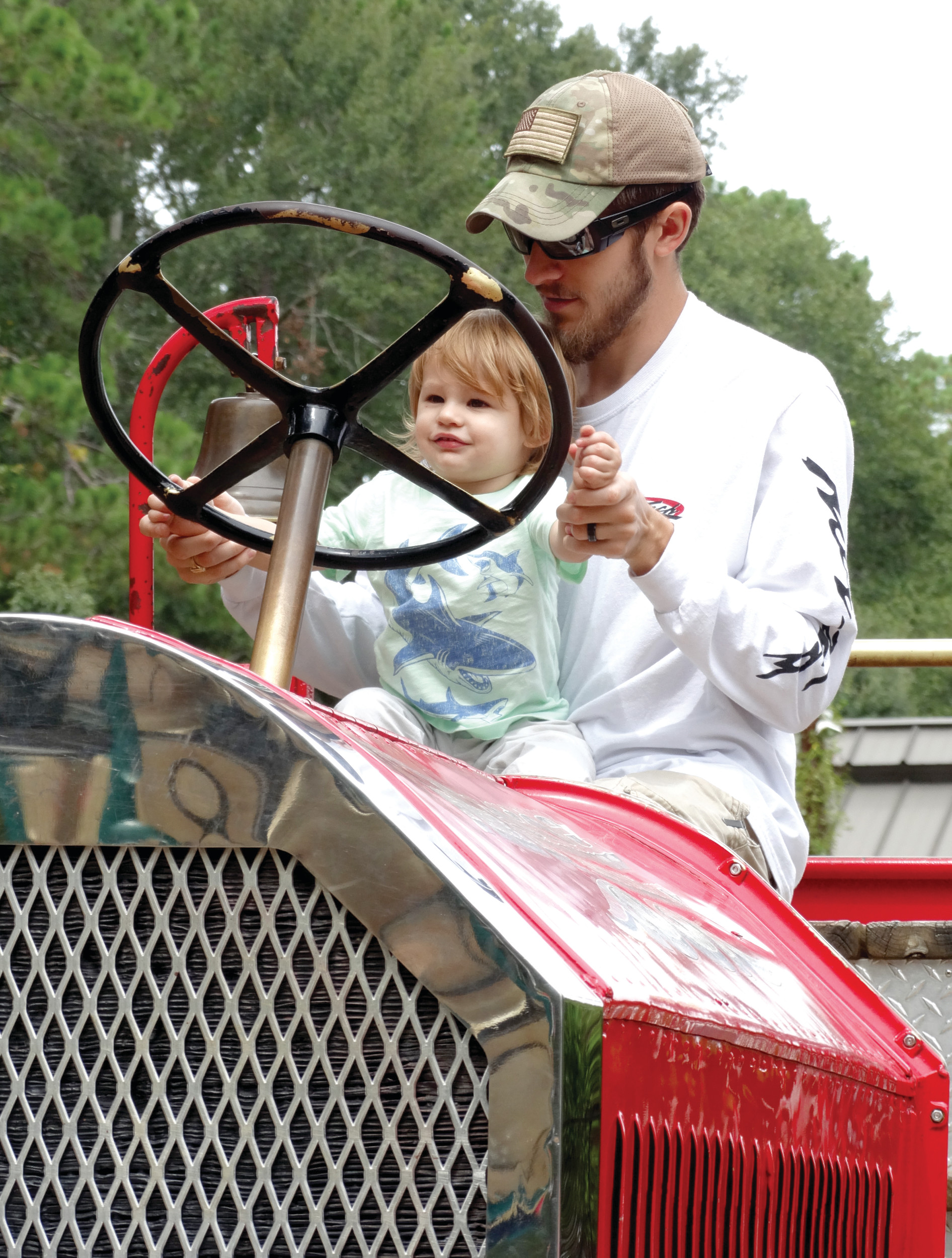 "Gunner Ceresa, 18 months, ""drives"" the fire truck at the Swan Lake-Iris Gardens playground on Sunday afternoon with the help of his father, Adam Ceresa. Adam, his wife, Tonya Ceresa, and Adam's sister, Sarah Ceresa, evacuated Cape Coral, Florida, before Hurricane Irma and stayed with relatives in Sumter. The 1924 Seagrave Fire Truck was in use in Sumter for 30 years, and in the 1960s, it was placed at the Swan Lake playground. The truck was completely overhauled in 2013 thanks to G&G Metal Fabrication owner Tom Garrity, Bailey Automotive, Carolina Truck and Trailer, the City of Sumter and Aycock Richardson Monument."