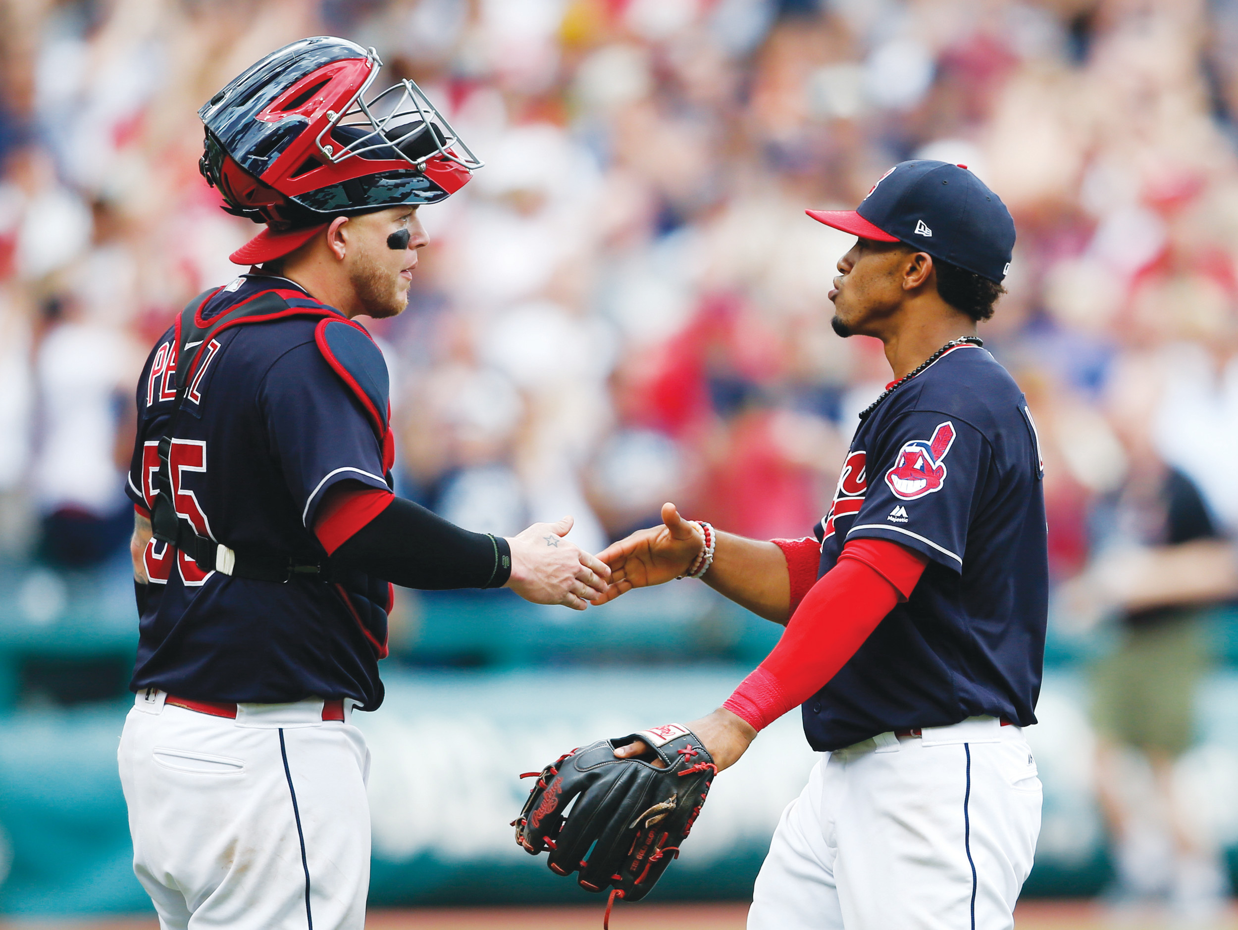 Cleveland's Roberto Perez, left, and Francisco Lindor celebrate a 5-3 victory over Detroit on Wednesday at Progressive Field in Cleveland. The Indians set the American League record with their 21st consecutive victory.