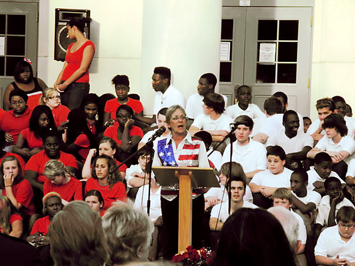 "Furman Middle School choral director Linda Beck, the originator and director of Sumter School District's observance of National Anthem Day, speaks to the crowd gathered during a past celebration. Seated behind her are just a few of the district's middle school chorus students, who traditionally sing ""The Star-Spangled Banner,"" as well as several other patriotic songs."