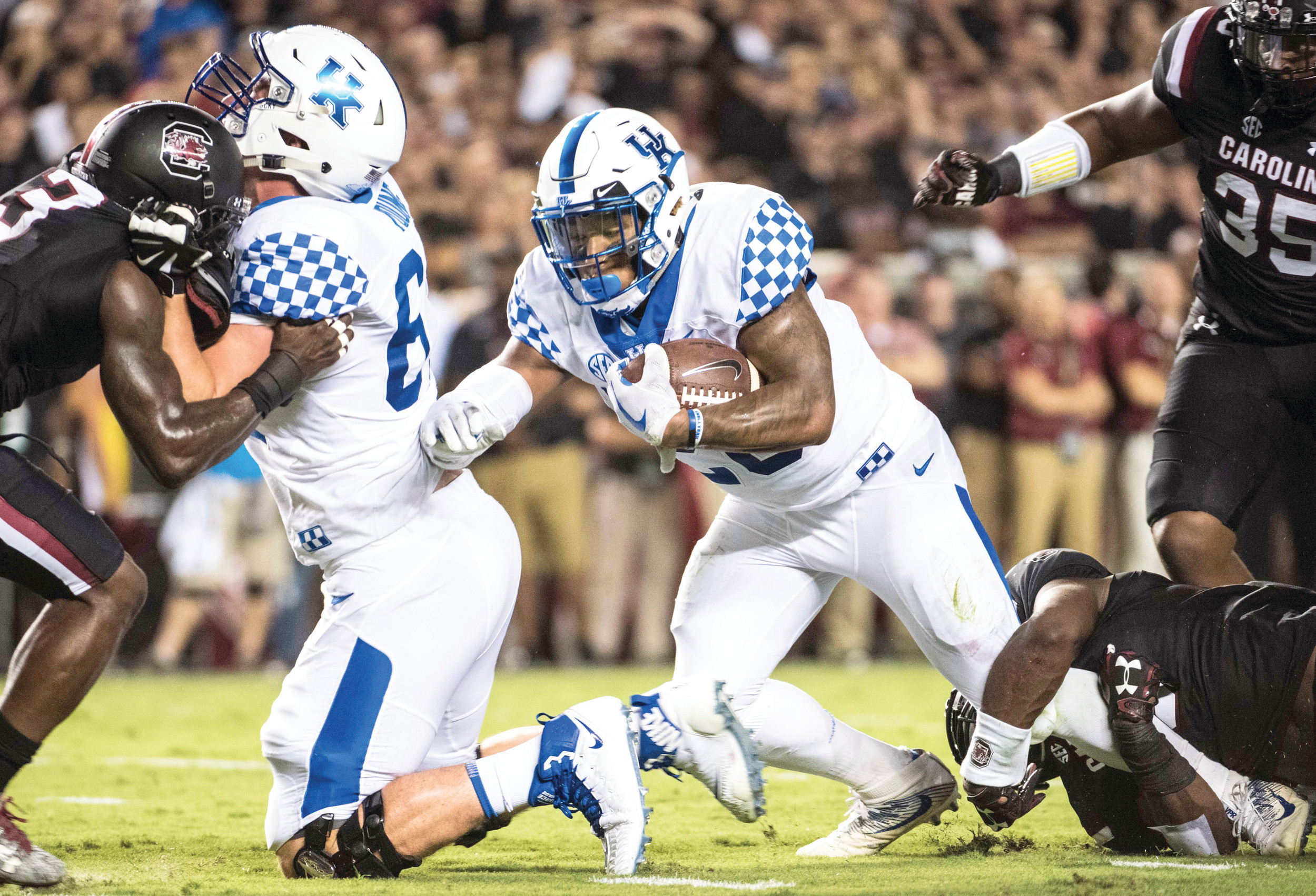 Kentucky running back Benny Snell Jr., center, fights through South Carolina defenders for more yardage during the Wildcats' 23-13 victory on Saturday in Columbia at Williams-Brice Stadium.