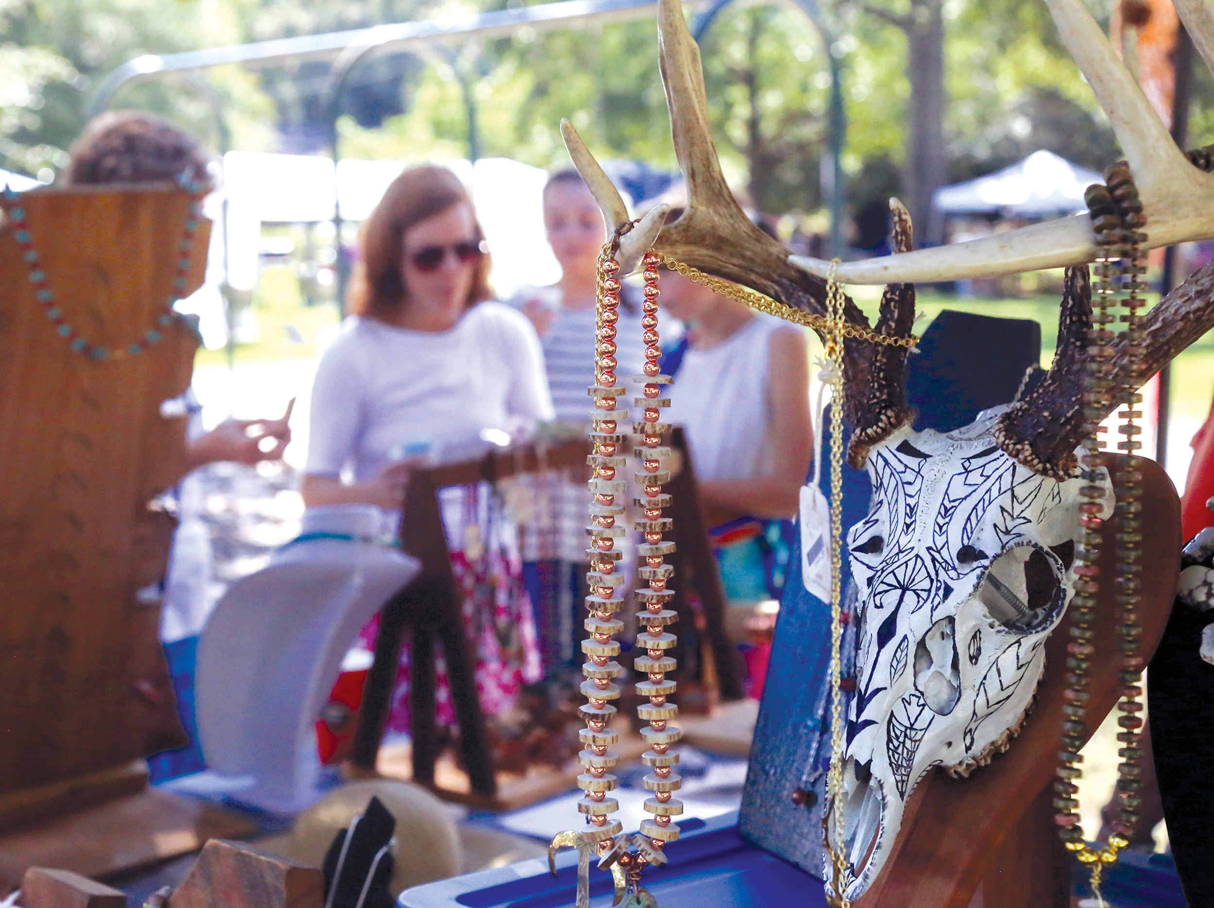 Visitors to the 2016 Art in the Park examine wood and metal art and jewelry at Shudwe Farms' booth. Artist Bryan DuRant will be back Saturday with more of his acclaimed work.