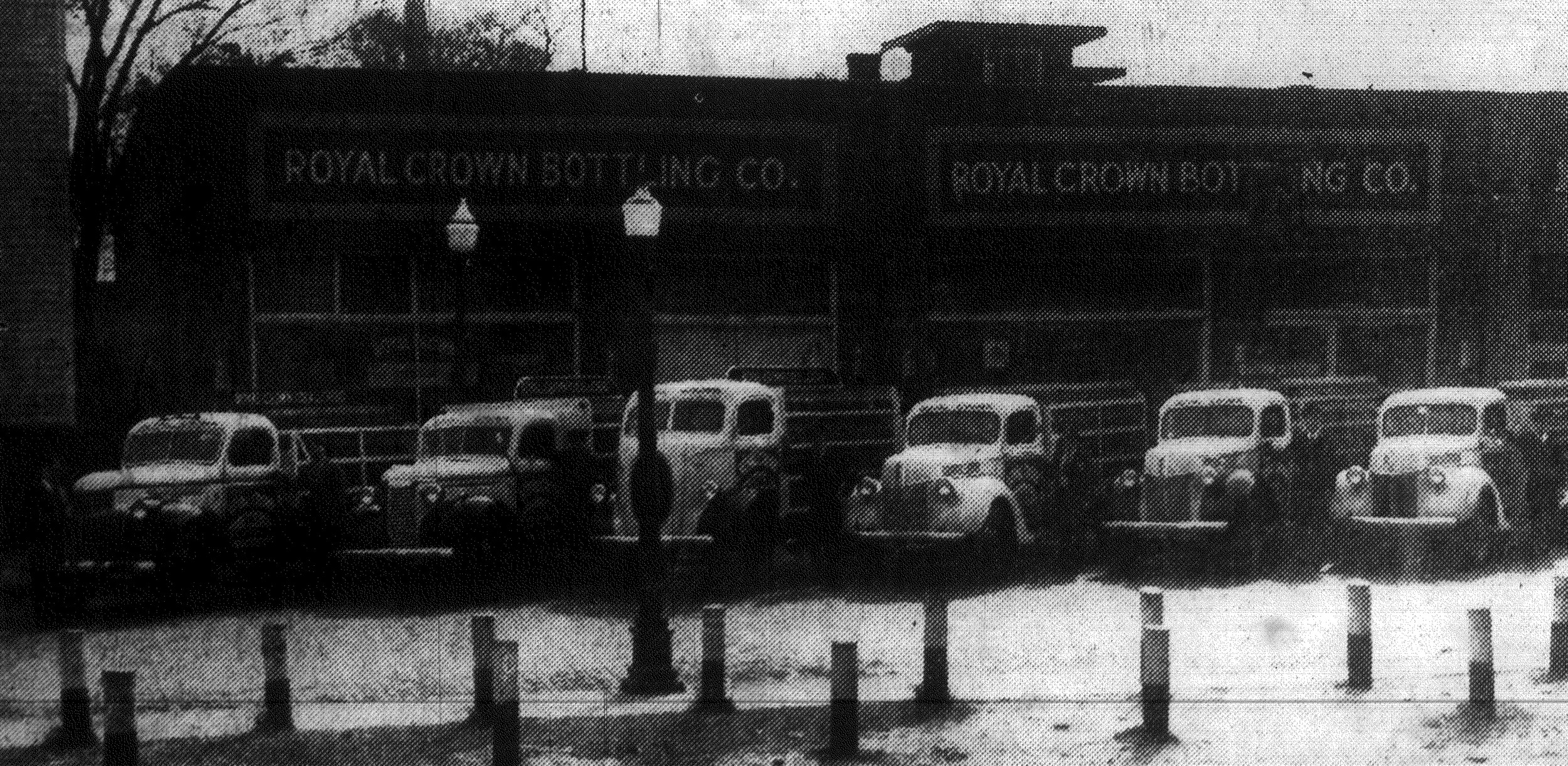 The fleet of Royal Crown Cola trucks is shown parked in front of the RC plant.