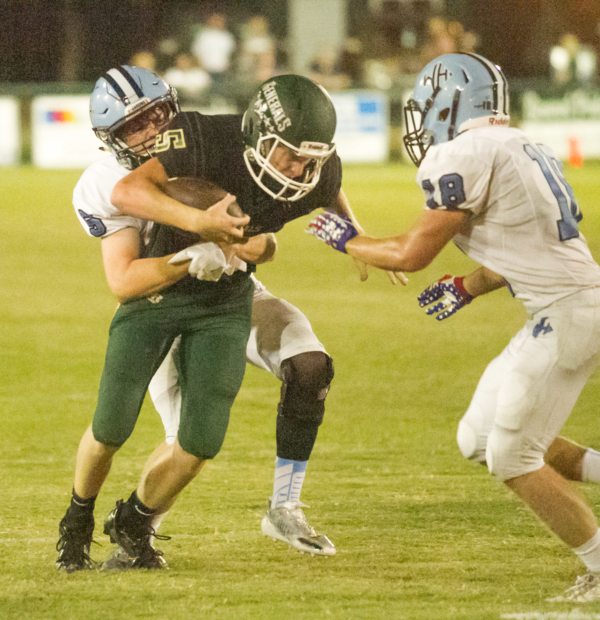 Thomas Sumter Academy's Mason Warren (5) fights for extra yardage as he's defended by Wilson Hall's Harrison Hudson, back, and Brandon Carraway during the Generals' 35-7 loss on Friday at General Field in Dalzell.