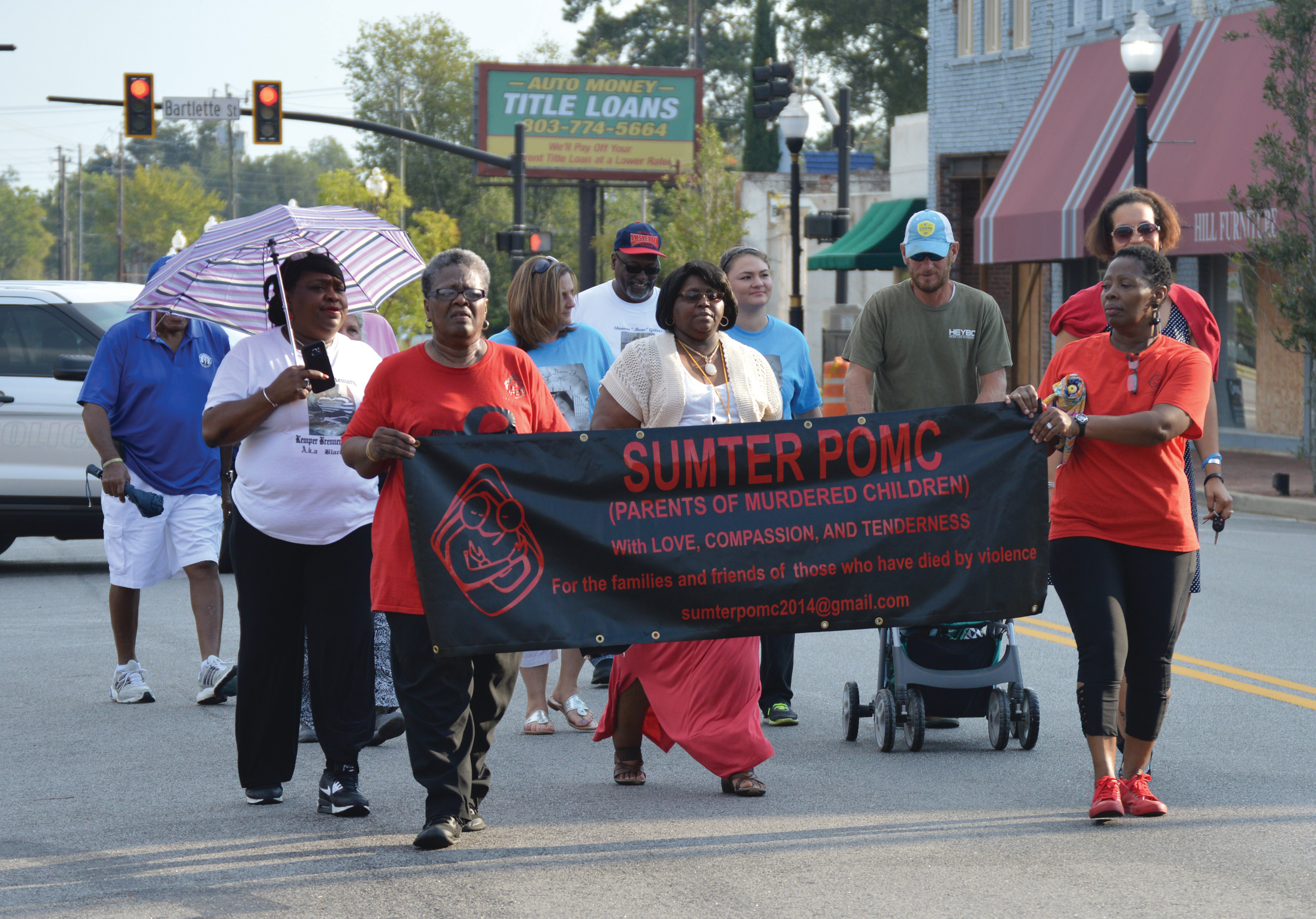 A group of supporters march down Main Street to the old Sumter County Courthouse during the 2017 A Day of Remembrance event on Thursday evening. The marchers consisted of family members of people who were murdered.