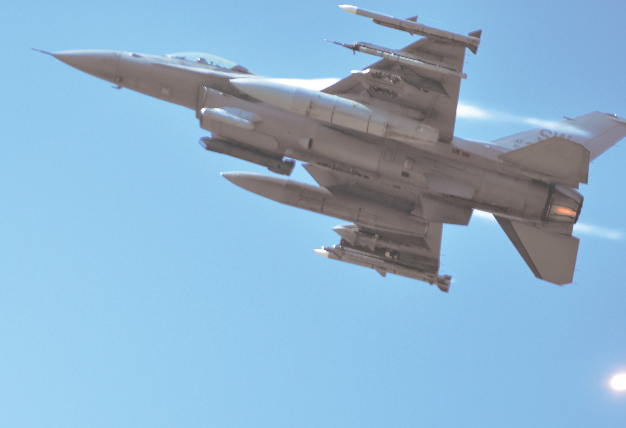 "An F-16 Fighting Falcone pulls up after firing its guns at a ground target on Friday at Poinsett Electronic Combat Range during the 77th Fighter ""Gambler"" Squadron's Range Day demonstration. The flare released by the aircraft as it fires is visible in the lower right corner of the image."