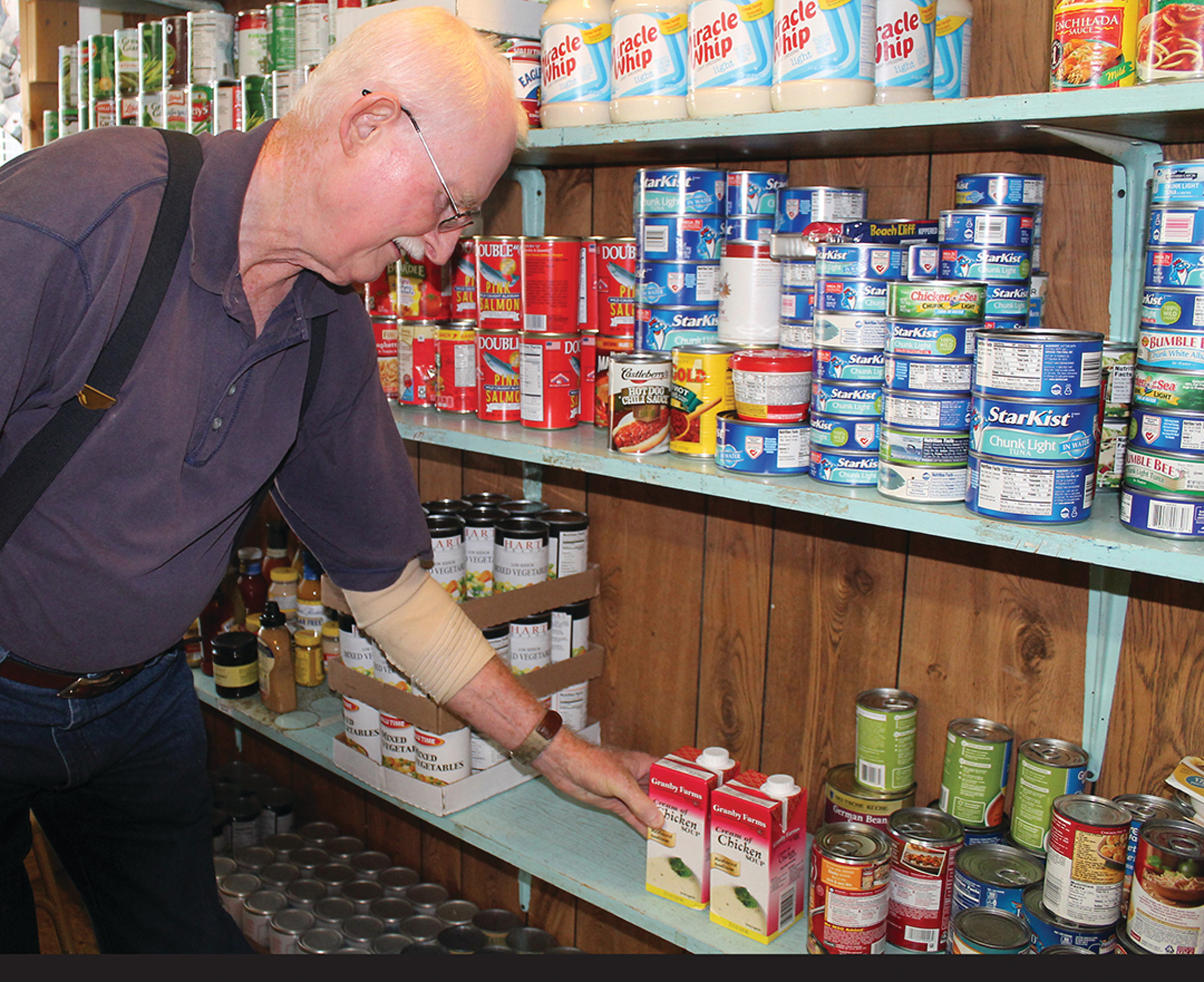 Gerald Winstead, a weekly volunteer at United Ministries of Clarendon County, stocks shelves with staples and other items that are necessities for the county's families in need of food items.