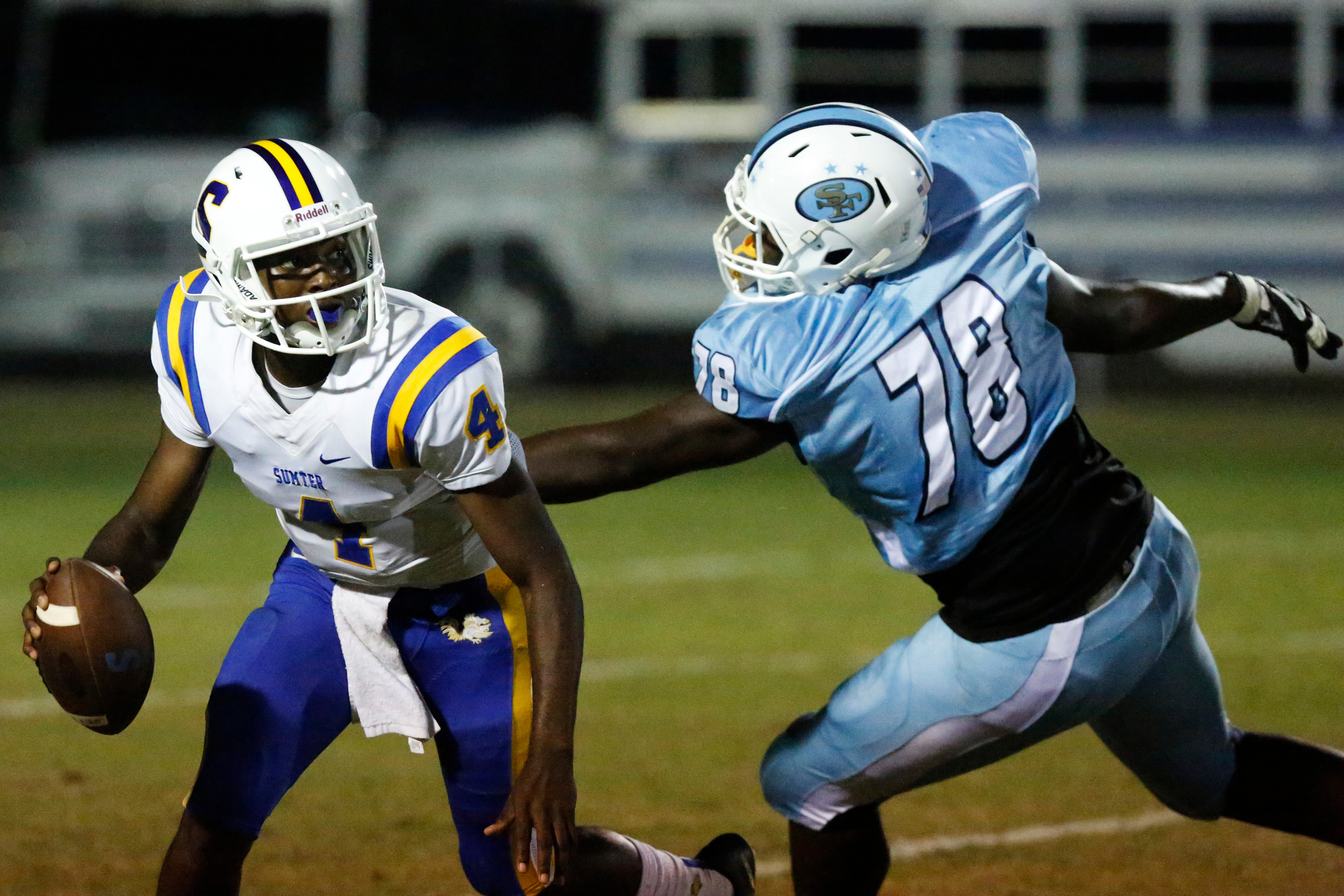 Sumter's Zykiem Jackson (4) tries to avoid South Florence's Sokova McDuffie during the Gamecocks' 31-20 victory on Friday at Florence's Memorial Stadium. Jackson ran for 117 yards and threw two touchdowns in the win.
