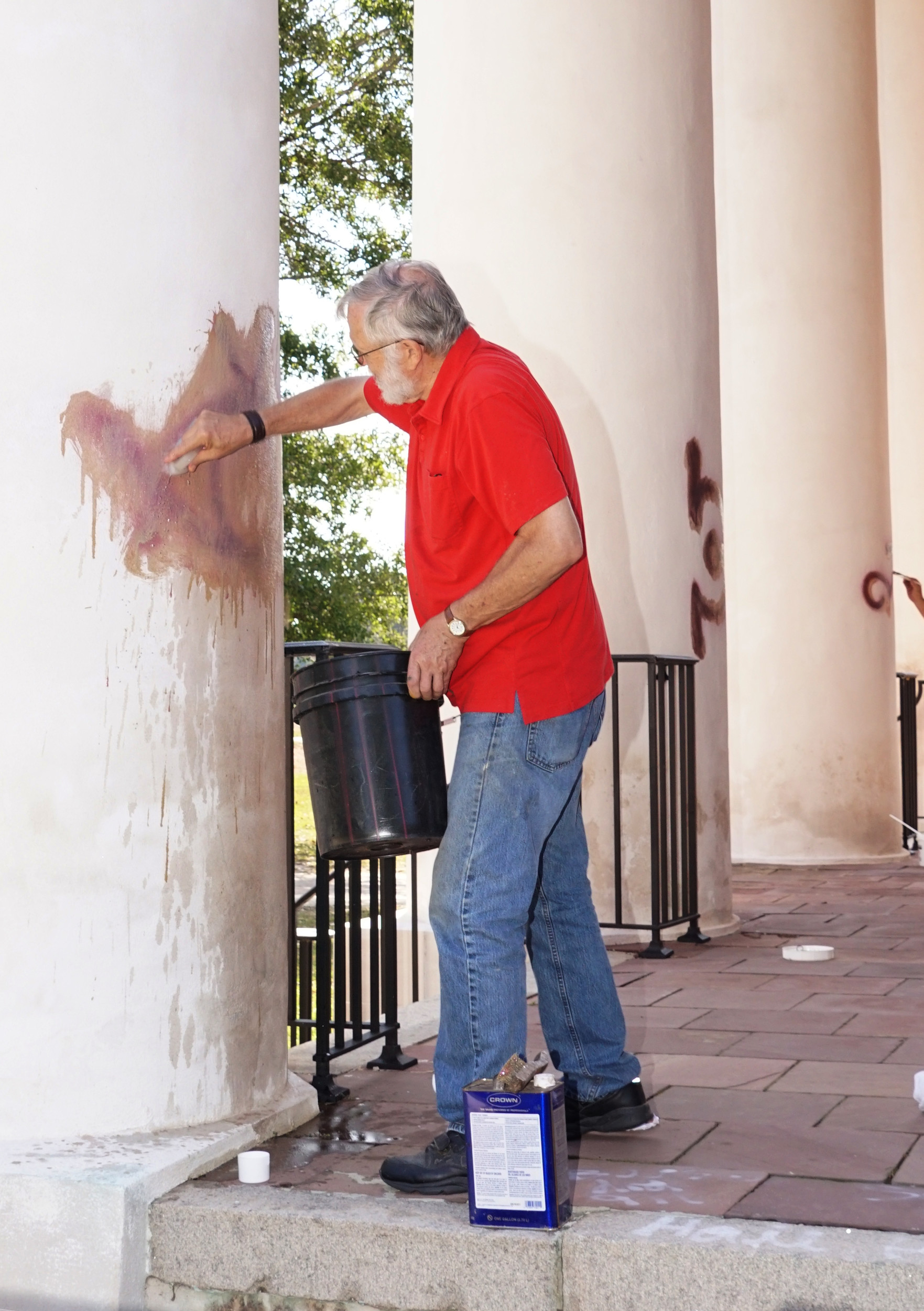 Slem Black River Presbyterian Church member Dick Dabbs cleans paint off a column at the church Friday after vandals painted satanic and other symbols on the church some time the previous night.