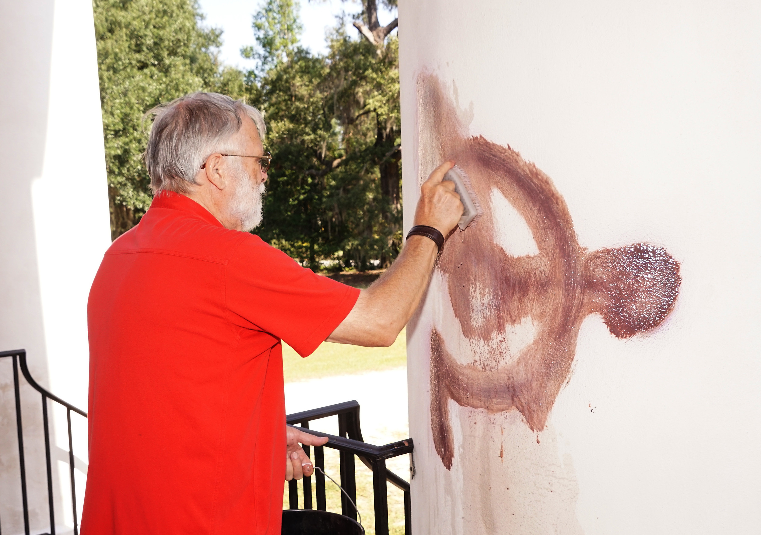 Salem Black River Presbyterian Church member Dick Dabbs cleans paint off a column at the church Friday after vandals painted satanic and other symbols on the church some time the previous night.