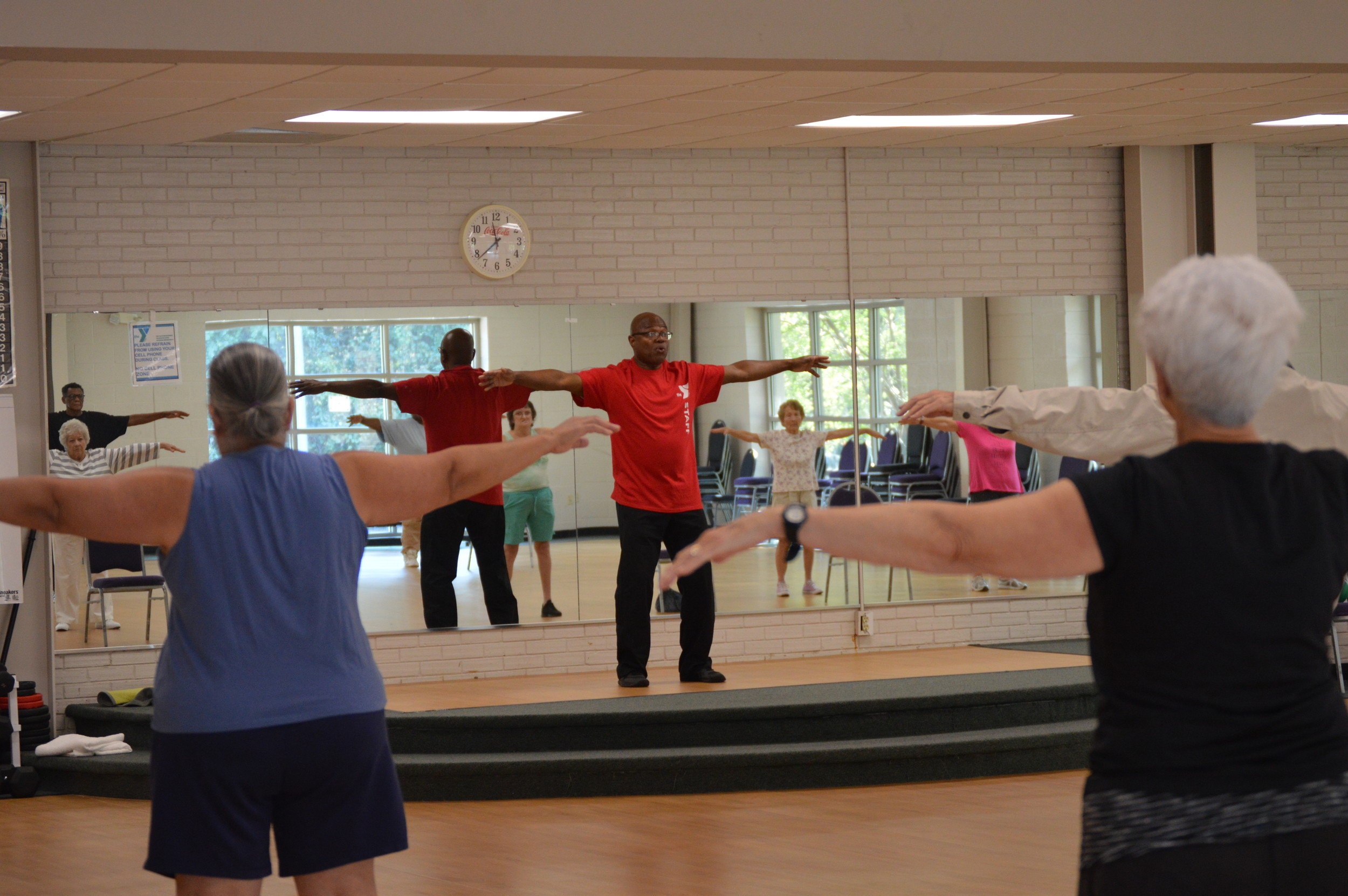 Students do a stretching and breathing exercise during Joseph Whiting's Tai Chi class at Sumter Family YMCA on Friday.