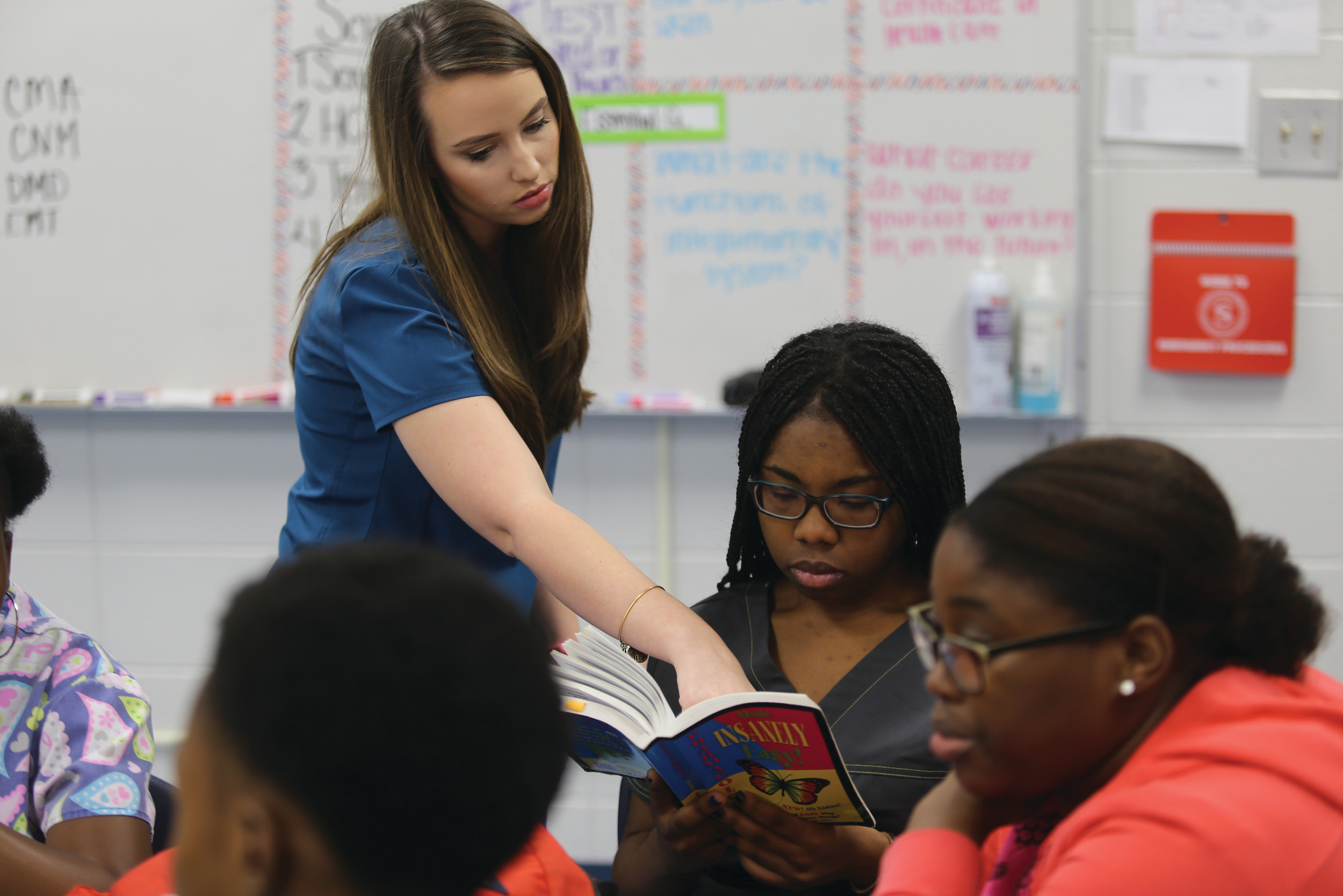 Sumter Career and Technology Center teacher Tiffany Morris goes over drug classifications from a textbook with Sumter High School senior Heather Brown on Friday as other students look on at the center.
