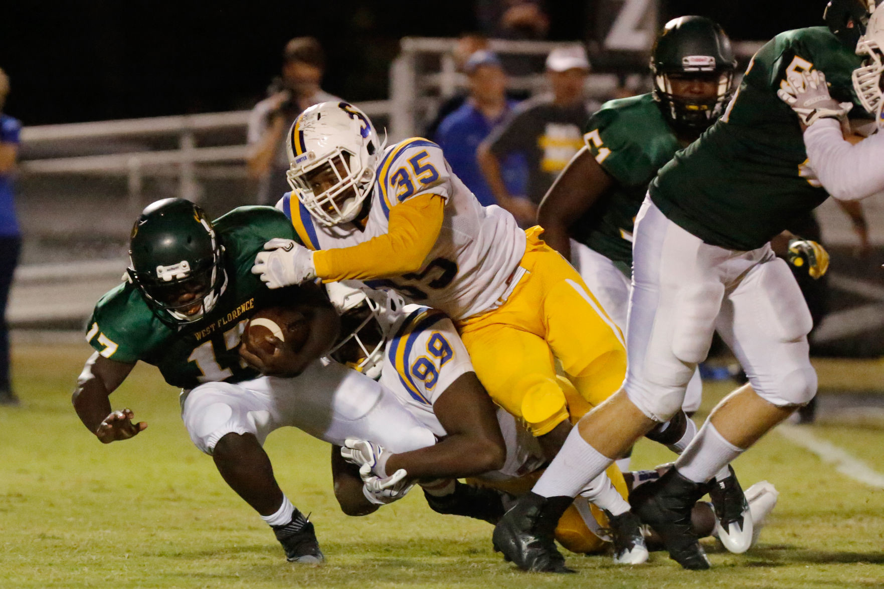Sumter defensive tackle Ronald McGee (99) and linebacker Andre Amaker (35) take down West Florence running back Ailym Ford in the Gamecocks' 44-6 victory on Friday at War Memorial Stadium in Florence.