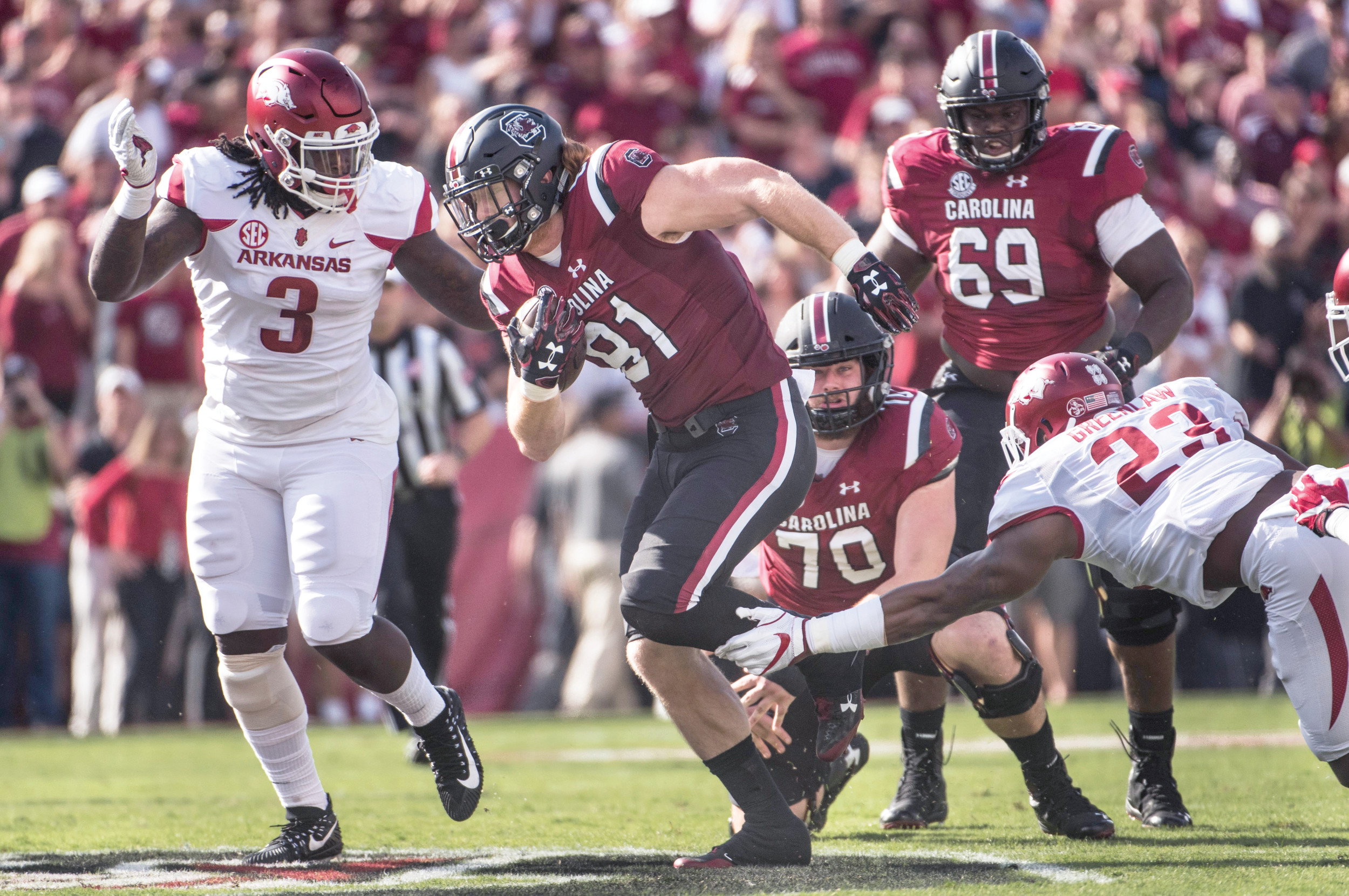 South Carolina tight end Hayden Hurst (81) runs as Arkansas defensive lineman McTelvin Agim (3) and Dre Greenlaw (23) defend during the Gamecocks' 48-22 victory on Saturday at Williams-Brice Stadium in Columbia.