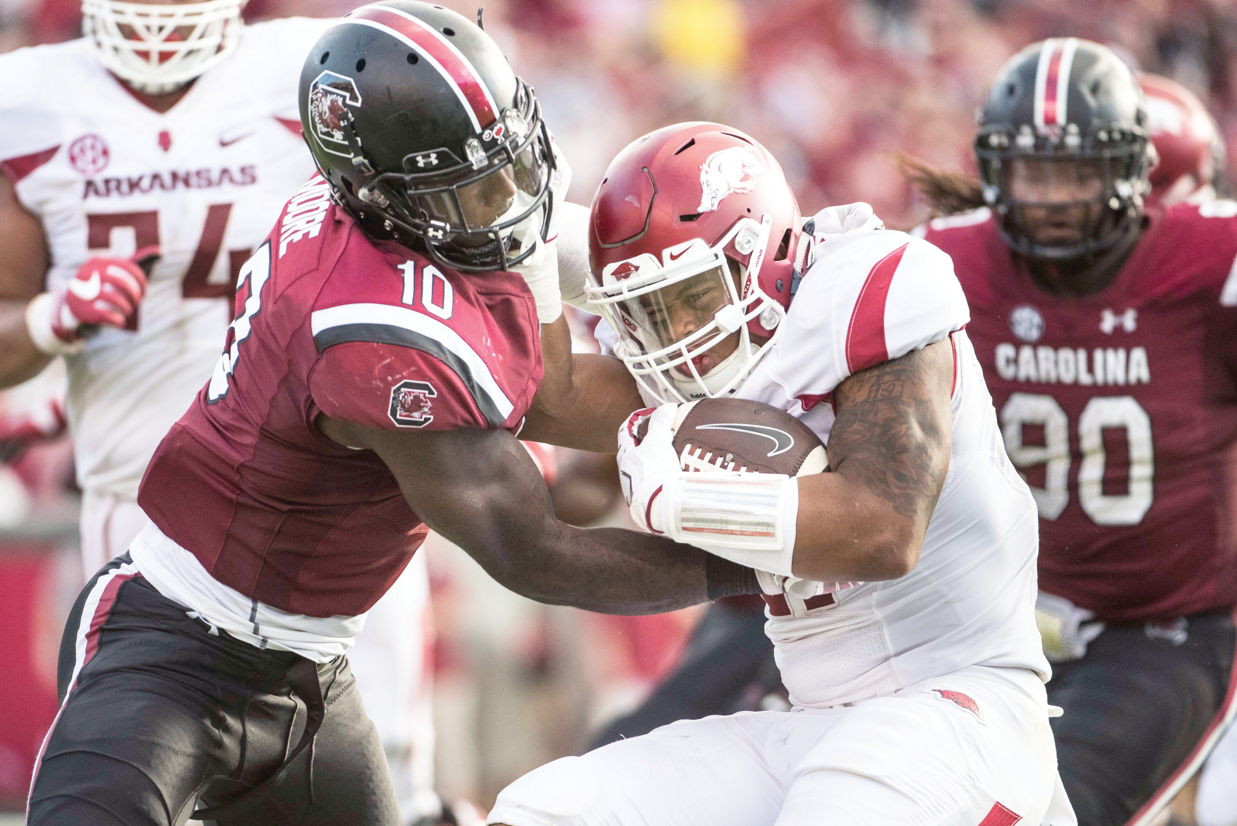 South Carolina linebacker Skai Moore, left, tackles Arkansas running back Devwah Whaley, center, during the Gamecocks' 48-22 victory on Saturday at Williams-Brice Stadium in Columbia.