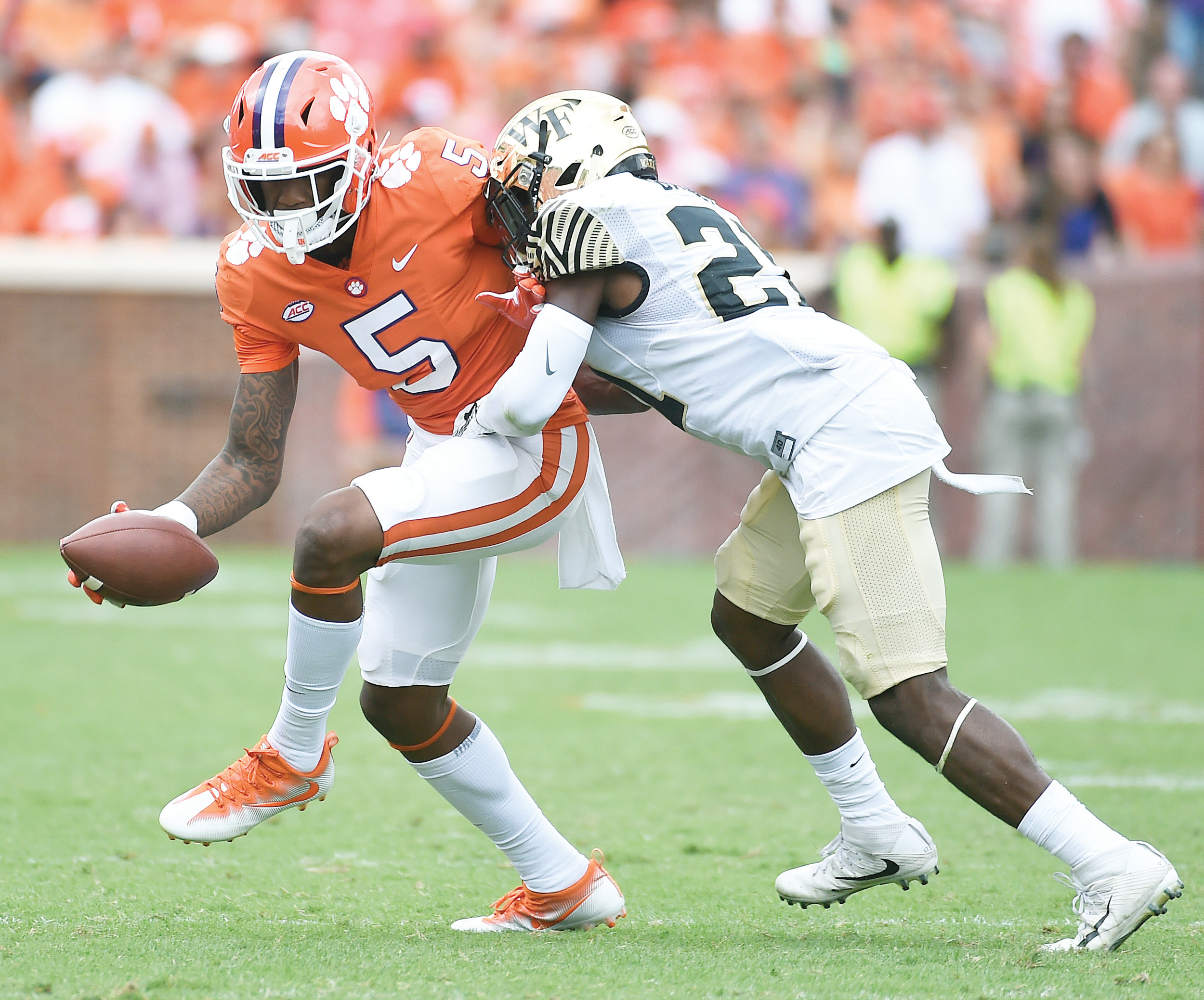 Clemson wide receiver Tee Higgins (5) tries to break free from Wake Forest defensive back Essang Bassey (21) during the Tigers' 28-14 victory on Saturday at Memorial Stadium in Clemson.