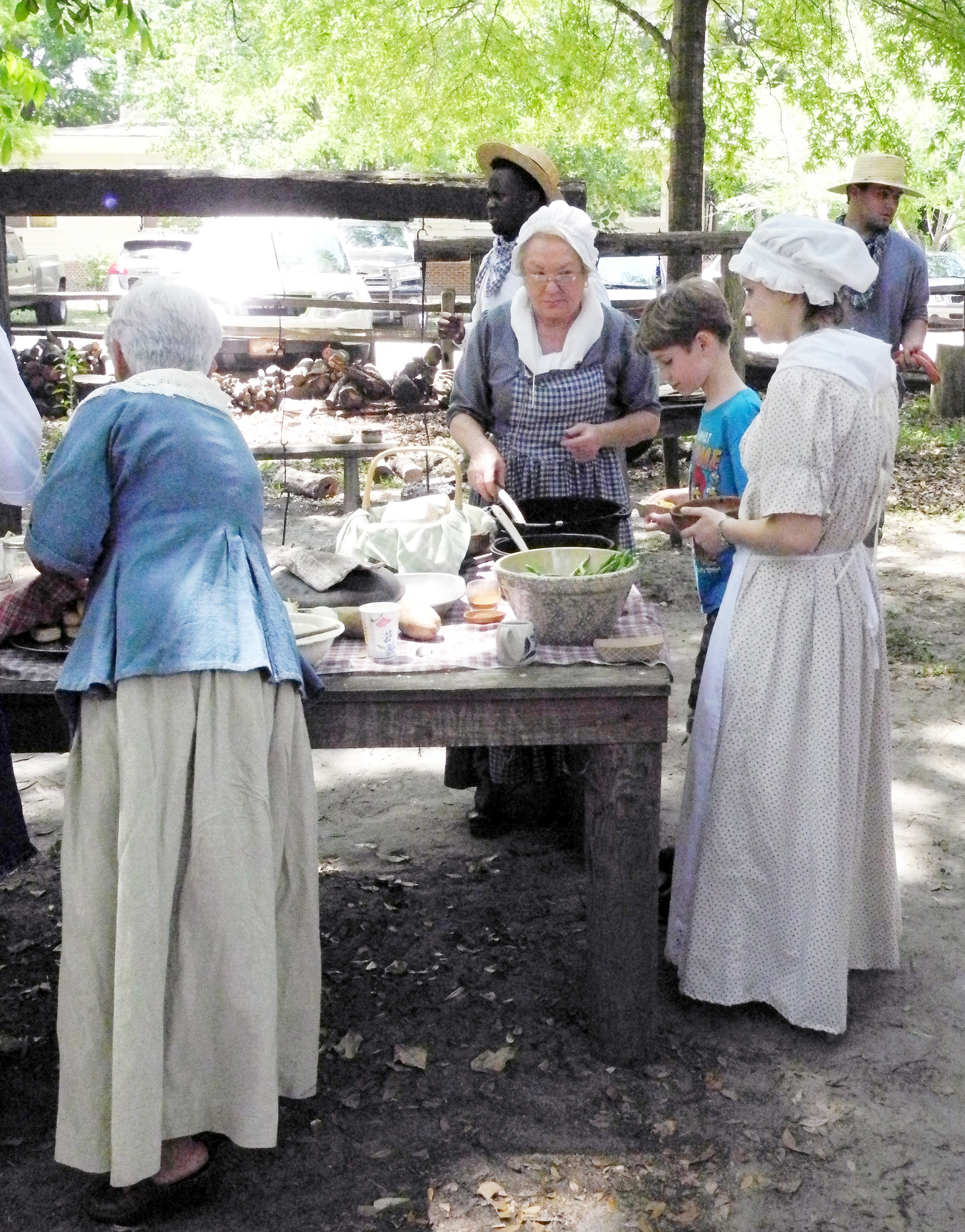 Deborah Watts, Sumter County Museum's Backcountry manager, serves up stew cooked over an open fire to guests at a Carolina Backcountry event. Museum staff and volunteers will be dressed in outfits like those worn by early Sumter-area settlers about the turn of the 19th century at the museum's Carolina Backcountry Harvest day program on Saturday.
