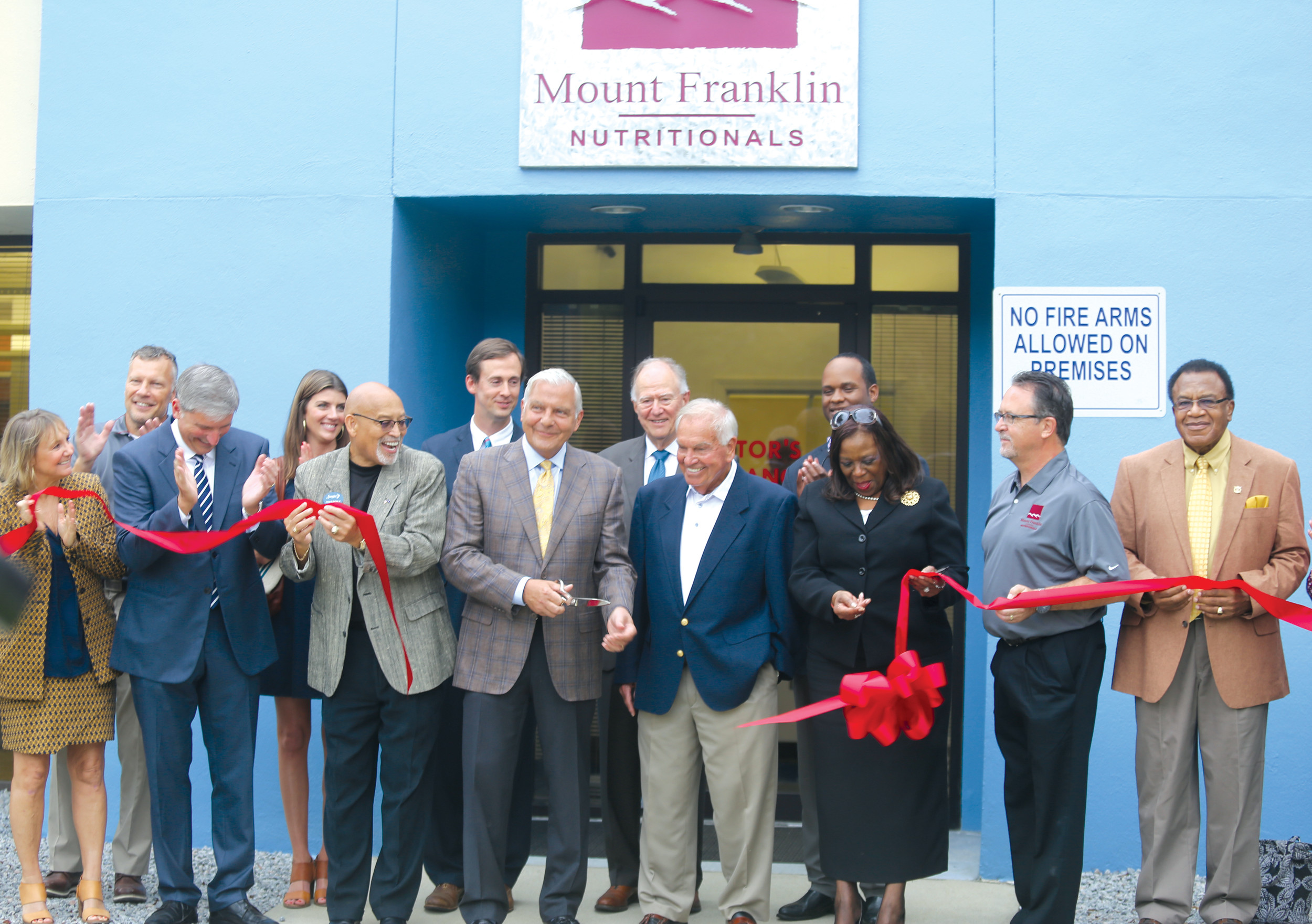 Mount Franklin Foods President and CEO Gary Ricco, with scissors in hand, cuts the ribbon Wednesday outside Mount Franklin Nutritionals' facility in Live Oak Industrial Park. Former New York Yankees great and Sumterite Bobby Richardson looks on at Ricco's left, along with other local officials.