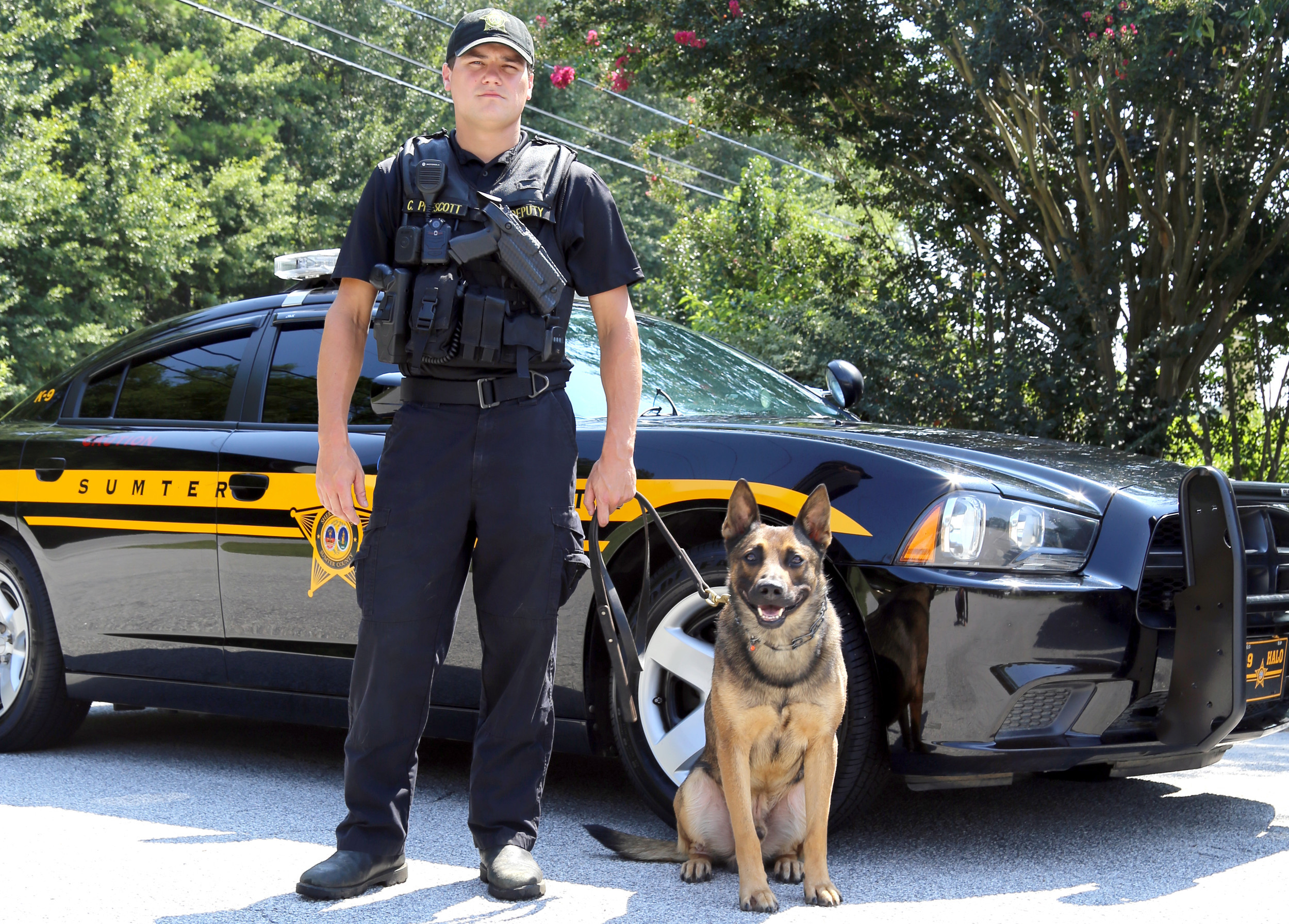 SUMTER ITEM FILE PHOTOK-9 Deputy Halo sits next to his handler Cpl. Cameron Prescott with Sumter County Sheriff's Office.