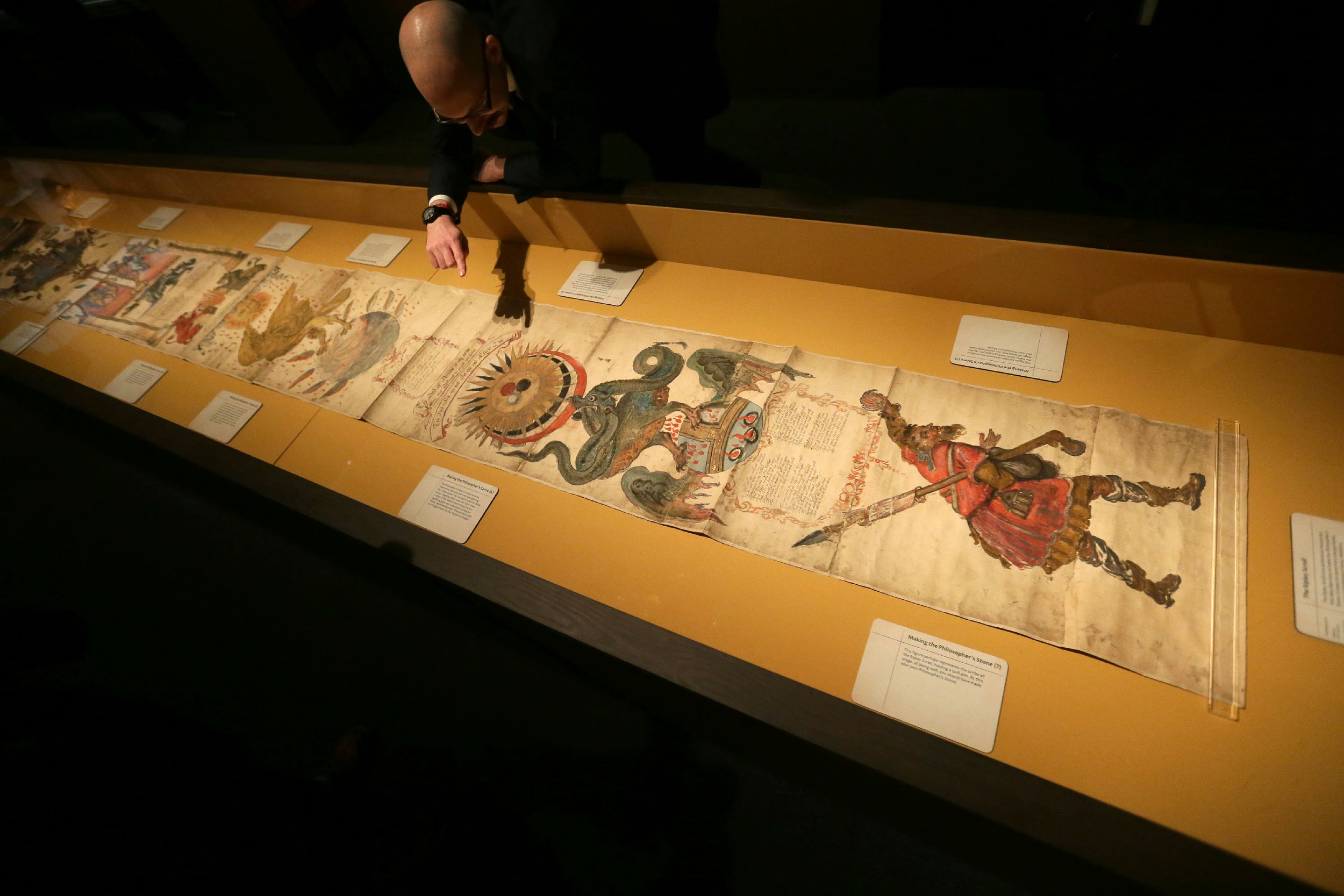 "A British Library staff member points at the Philosopher's Stone on the 16th-century Ripley Scroll, which describes how to make a Philosopher's Stone, at the ""Harry Potter - A History of Magic"" exhibition at the British Library in London."