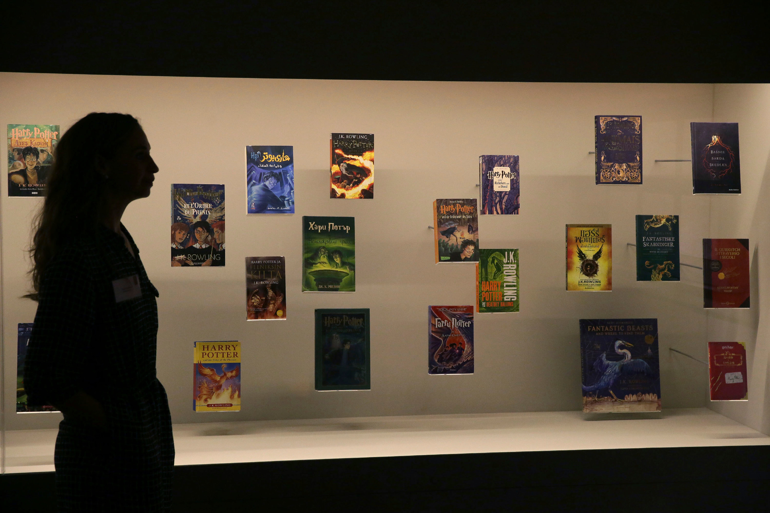 "A member of the British Library staff stands beside a display of Harry Potter books published in several languages at the ""Harry Potter - A History of Magic"" exhibition at the British Library in London."