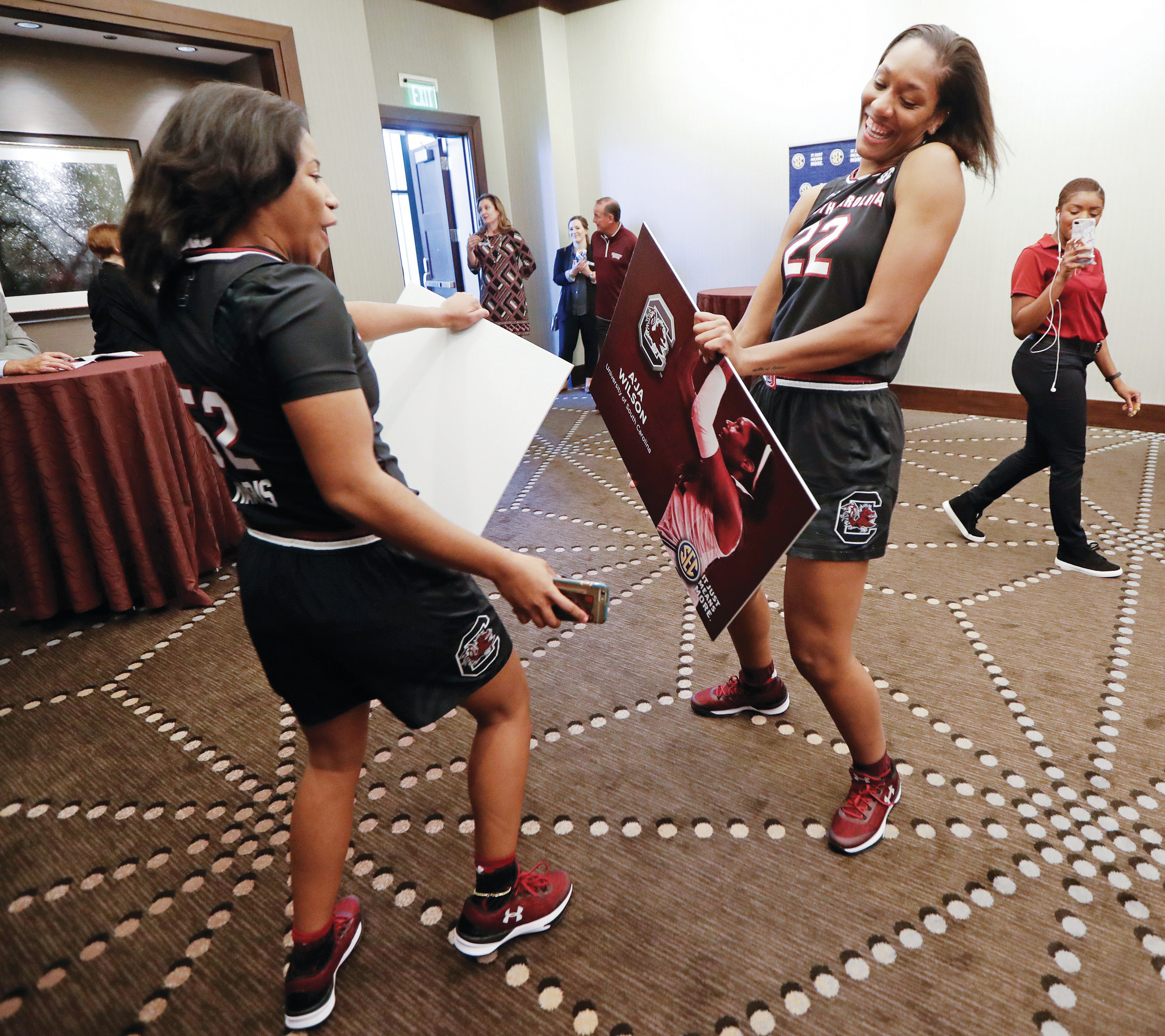 South Carolina players Tyasha Harris, left, and A'ja Wilson (22) dance while holding posters of themselves after finishing their news conference during the Southeastern Conference women's basketball media day on Thursday in Nashville, Tennessee.
