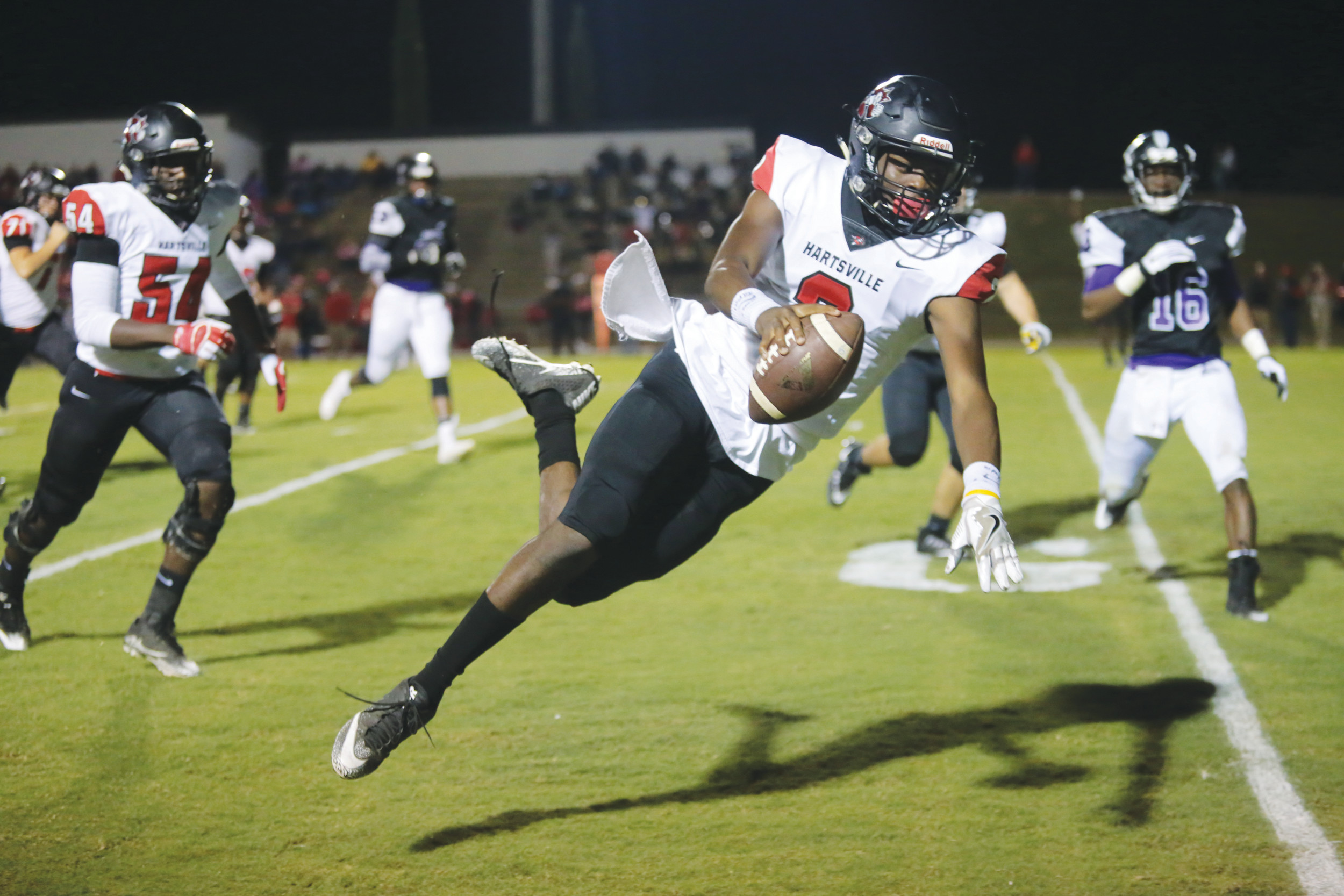 Hartsville quarterback A.J. Joyner finishes off a touchdown run in the first quarter of the Foxes' 48-0 win over Crestwood on Friday at Donald. L. Crolley Memorial Stadium.