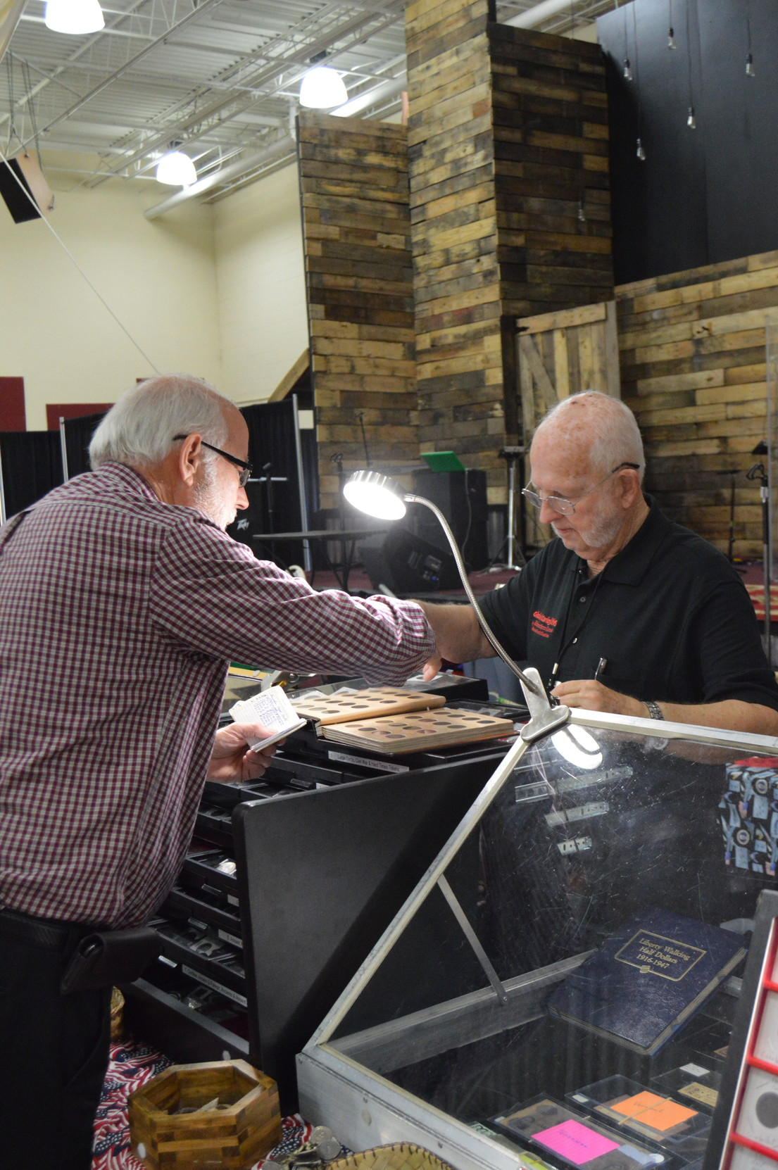 Don Cann, right, discusses his extensive coin collection with a visitor during the annual Sumter Coin Show on Saturday.