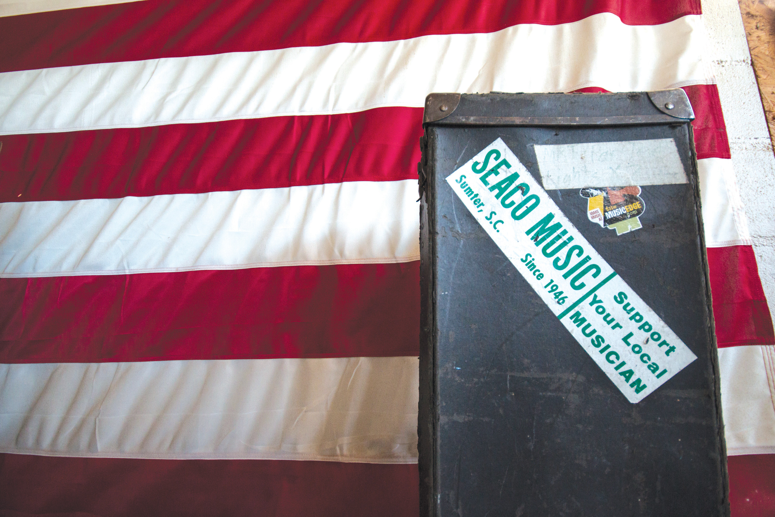 "A box adorned with a SEACO Music sticker featuring ""Since 1946"" sits in front of SEACO's huge American flag. SEACO thanks its loyal customers for supporting local music and musicians, and it looks forward to continuing the tradition across town."