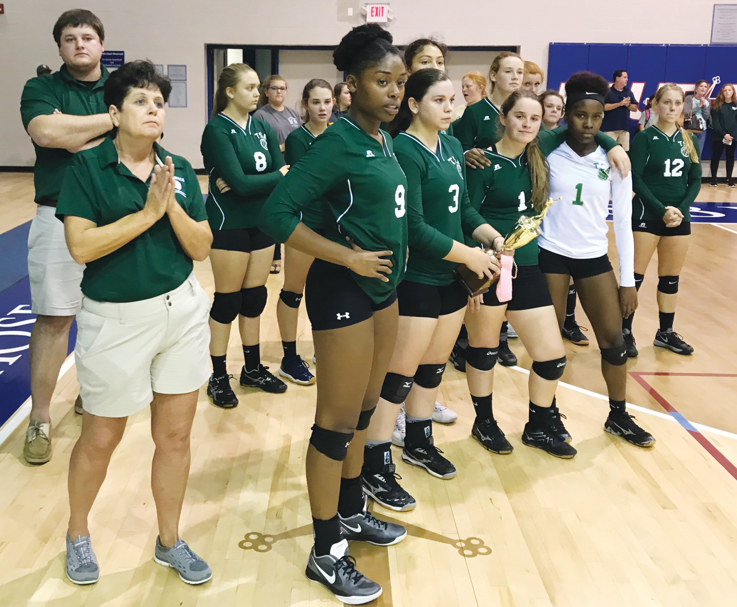 Thomas Sumter Academy head volleyball coach Gwen Herod, front left, stands with her team as the SCISA 2A volleyball championship trophy is awarded to the Generals' opponents, Spartanburg Christian, on Tuesday at Presbyterian College in Clinton.