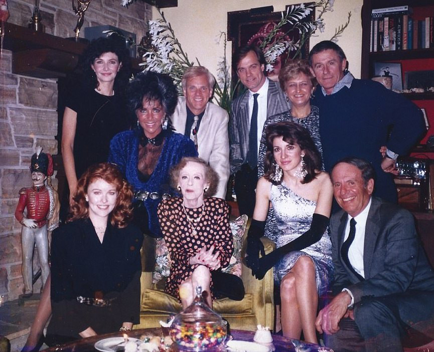Bette Davis, Kathryn Sermak to her right, celebrating 87th birthday with friends.