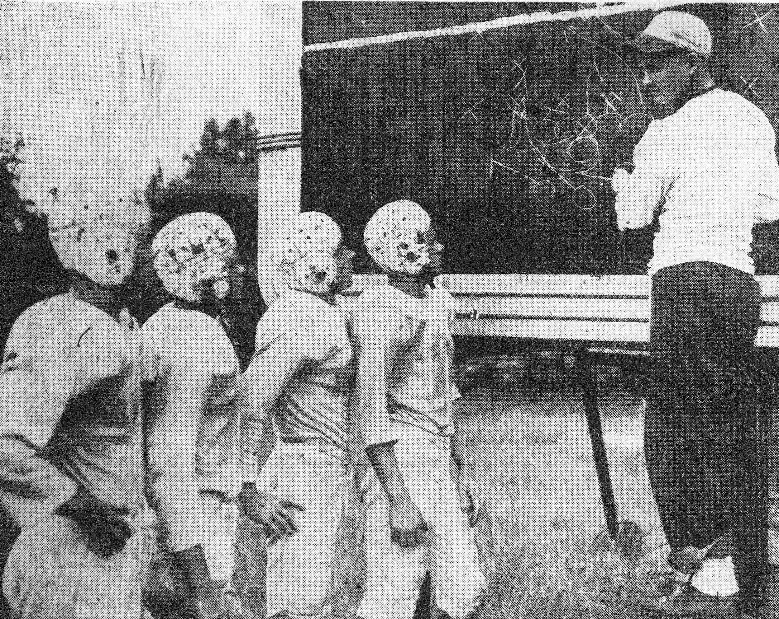"SUMTER ITEM FILE PHOTO  ""Skull practice"" is an important part of the pre-season football training for backfield men of the Sumter High squad. Getting inside dope on a new play from Coach Hutch Hutchinson, right, are left to right, Dale Garrison, right halfback; Laverne Hill, fullback; Russell Sutton, left halfback; and Marion ""Sugar"" Cain, quarterback."