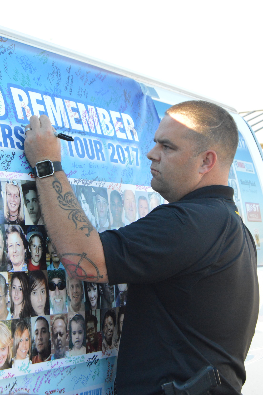 ADRIENNE SARVIS / THE SUMTER ITEM  Lt. Jeffrey Richardson with Sumter County Sheriff's Office signs a banner attached on the side of Community United Effort's vehicle during the organization's annual On the Road to Remember tour on Friday. The banner includes photos of missing and unidentified people.