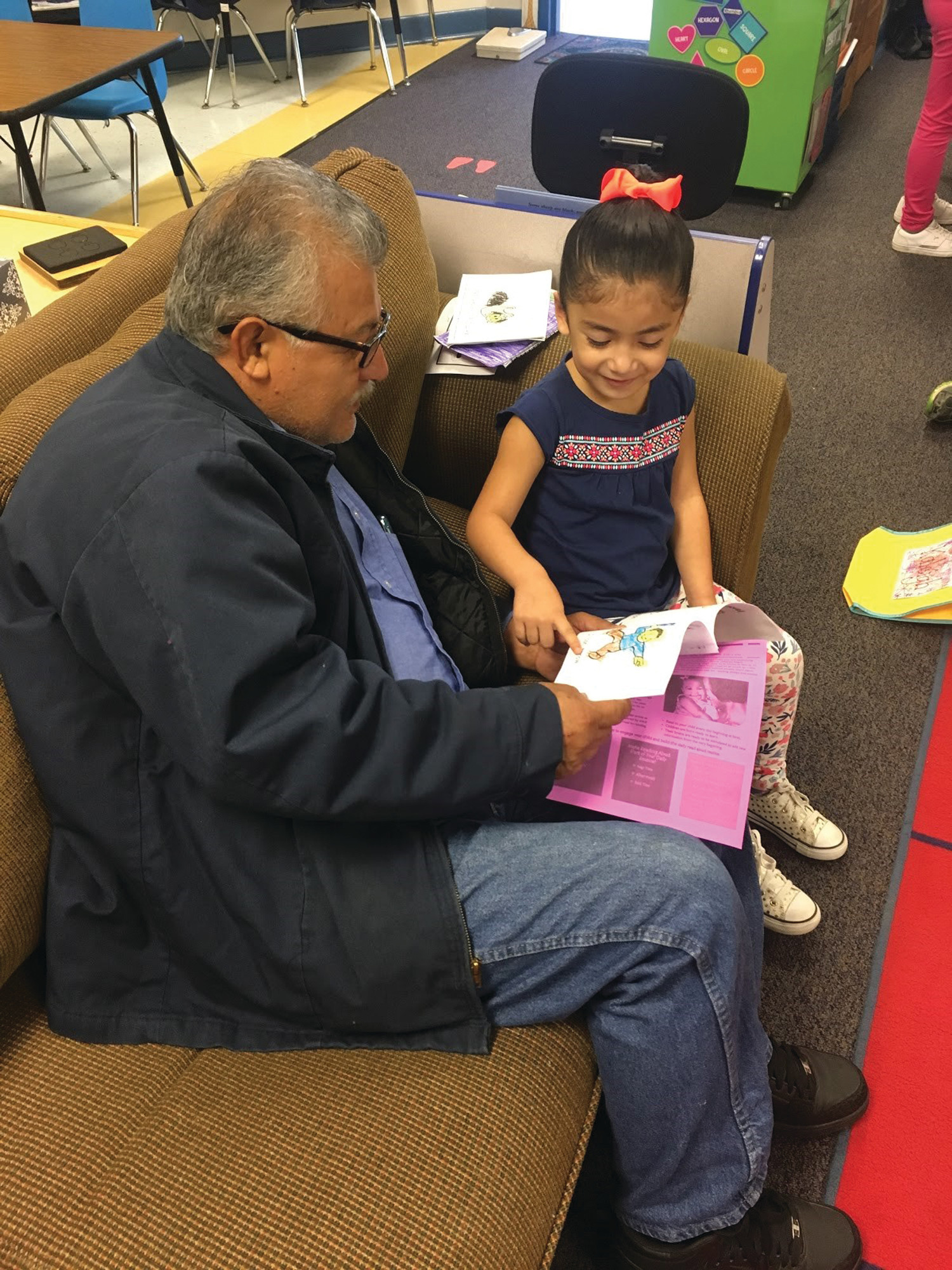 Bella Valdez, a kindergarten student at MECC, reads a book to her grandfather, David Valdez, during the Dine with Dudes event.