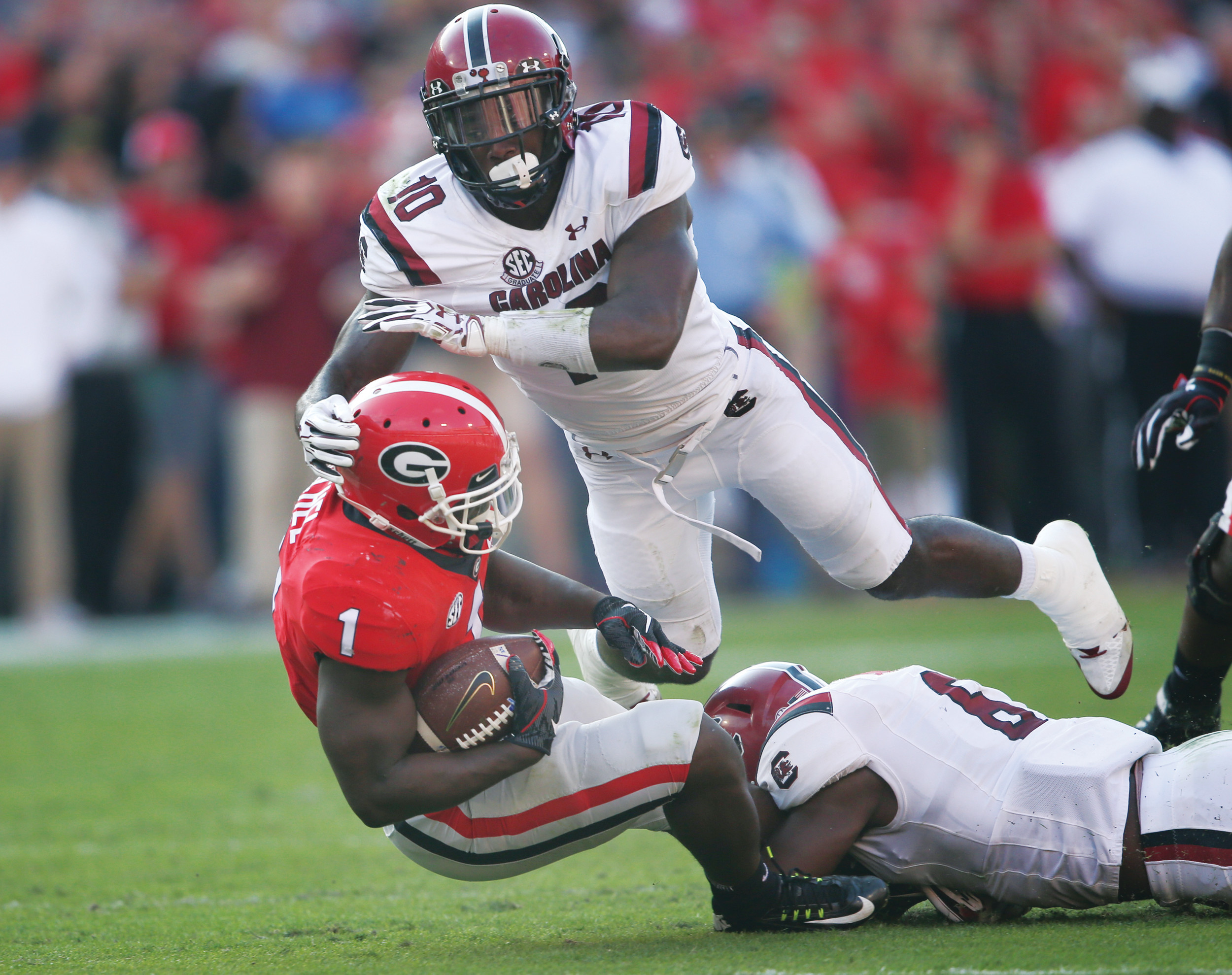 Georgia running back Sony Michel (1) is tackled by South Carolina linebackers Skai Moore (10) and T.J. Brunson (6) during the Bulldogs' 24-10 victory on Saturday in Athens, Georgia.