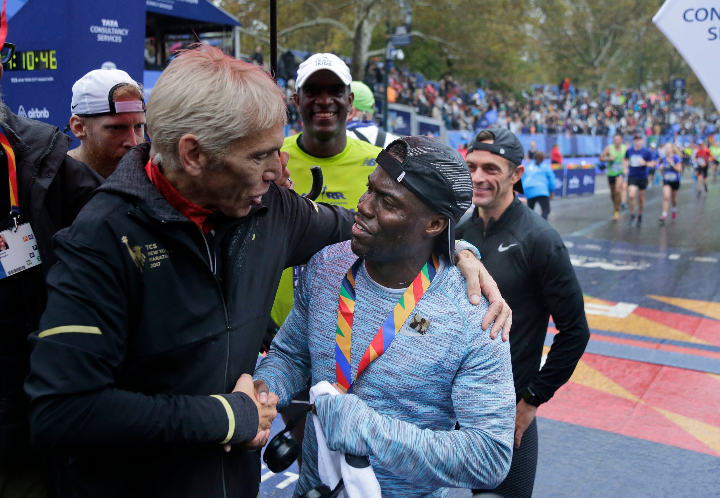 Marathon race director Peter Ciaccia, left, greets Kevin Hart as he crosses the finish line of the New York City Marathon on Sunday.