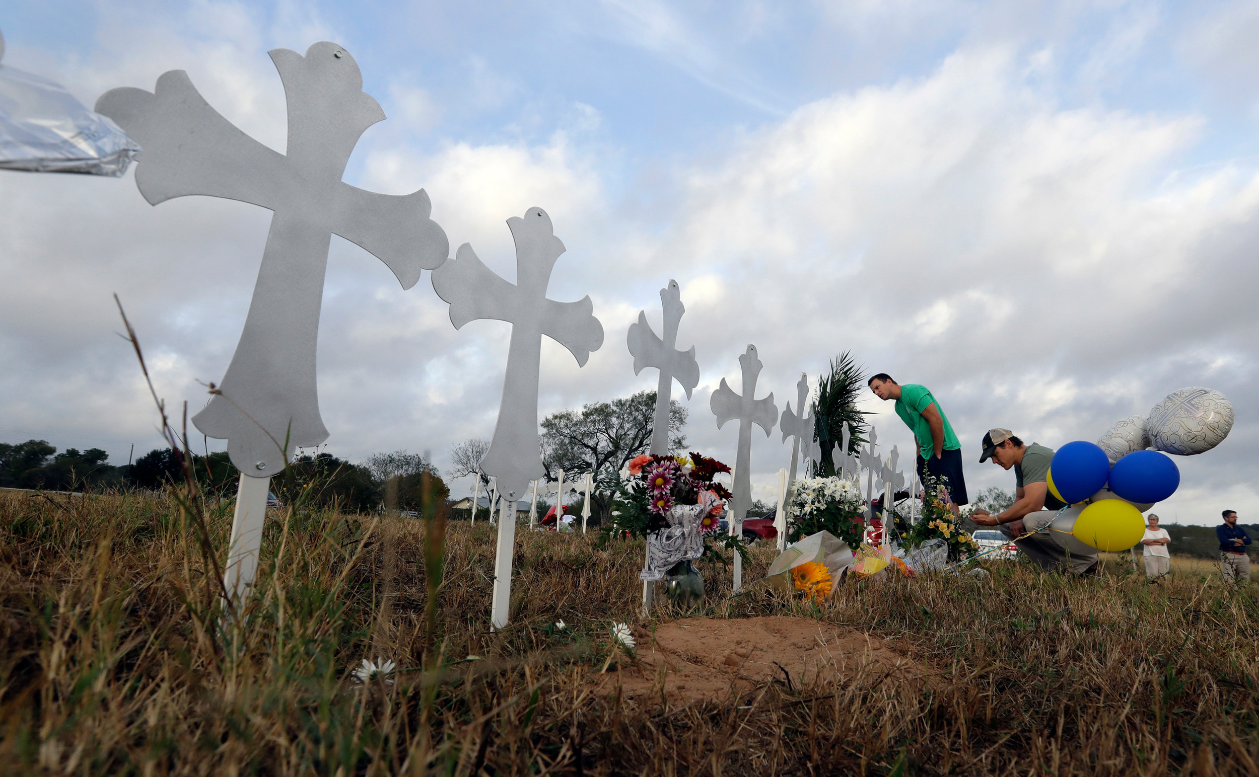 Kevin Blomstrum, left, and Kyle Dahlberg visit a makeshift memorial Tuesday for victims near the scene of a shooting at First Baptist Church of Sutherland Springs in Sutherland Springs, Texas. A man opened fire inside the church in the small South Texas community on Sunday, killing more than two dozen and injuring others.