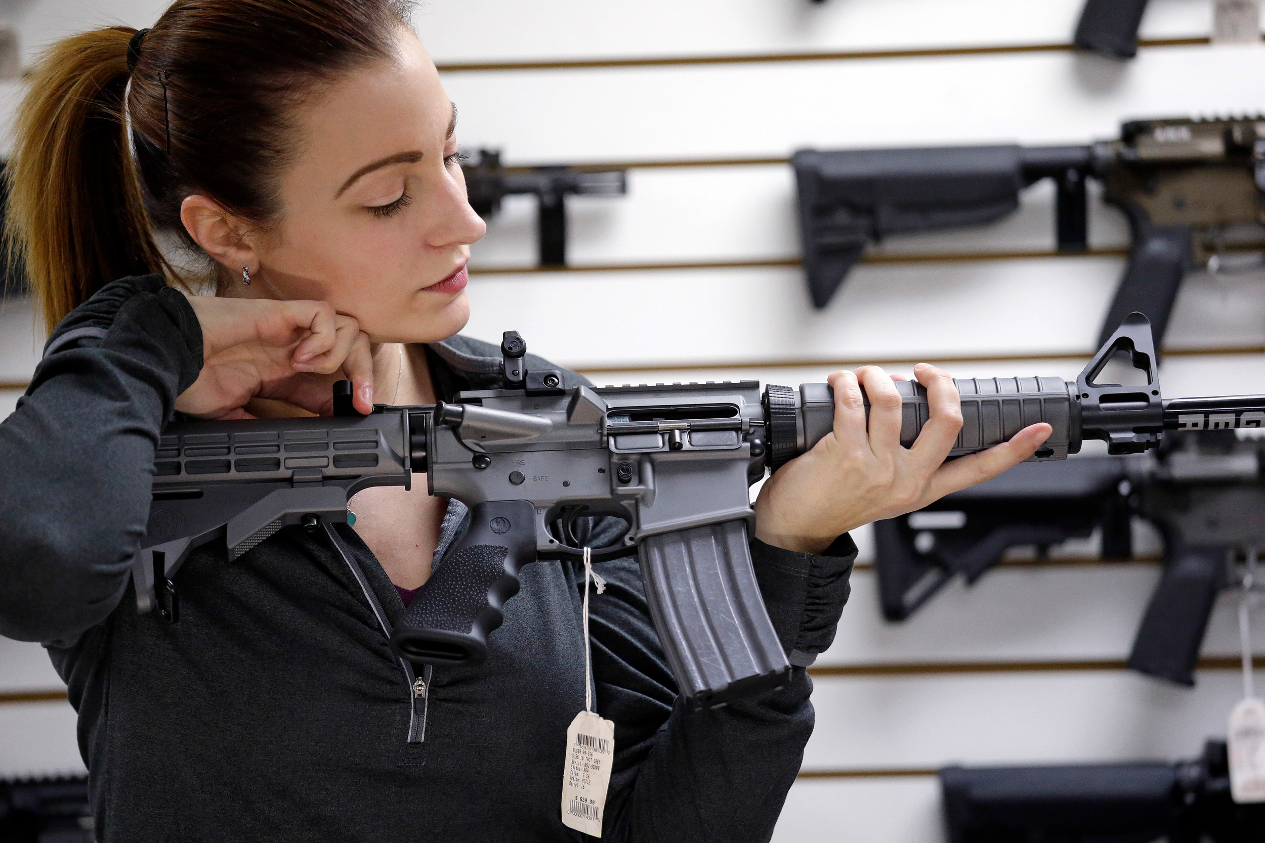 Gun shop owner Tiffany Teasdale-Causer demonstrates a Ruger AR-15 semi-automatic rifle - the same model used by the shooter in the Texas church massacre - at her shop in Lynnwood, Washington.