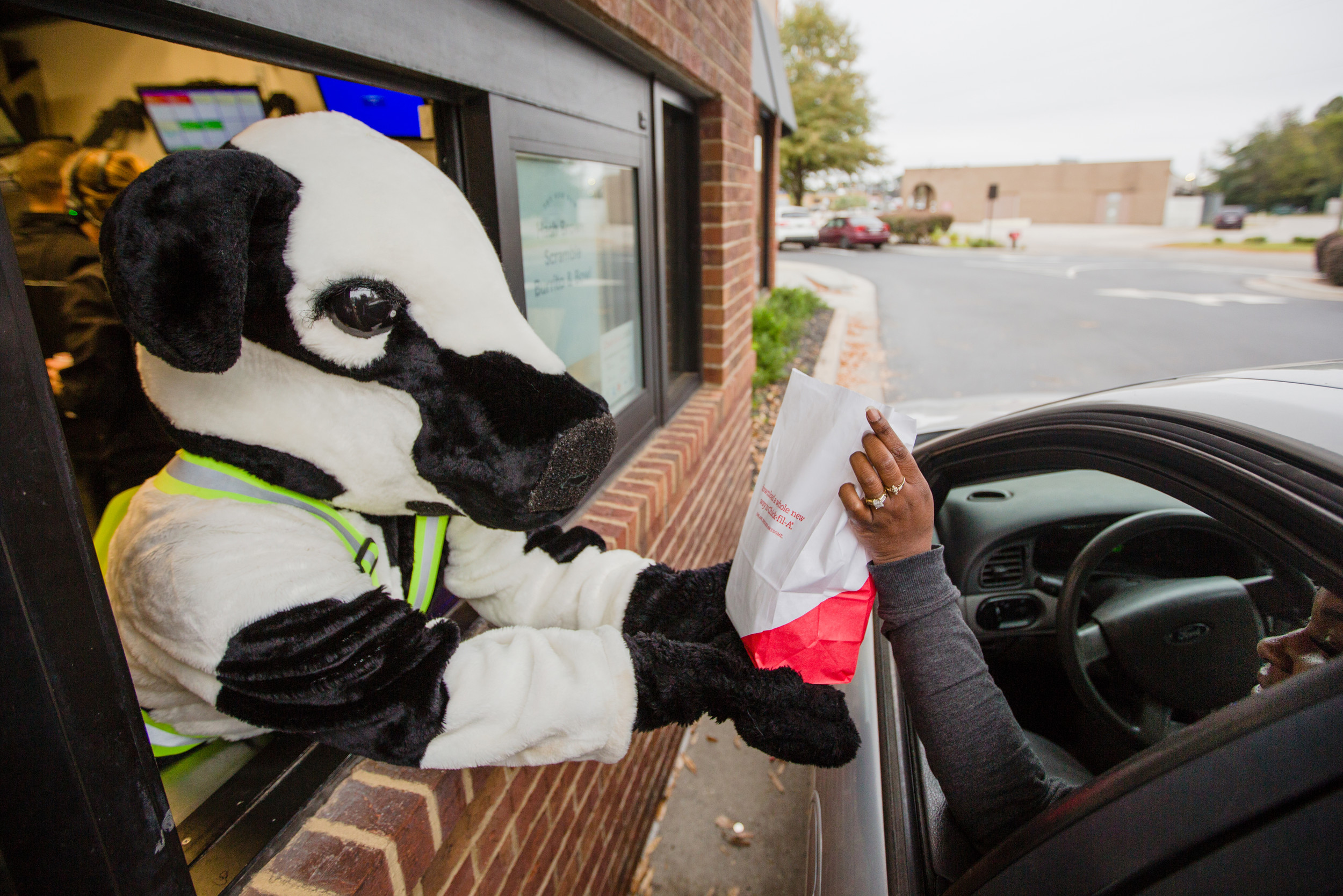 The Chick-fil-A Kid Cow hands out drive-thru orders during the grand reopening of the Broad Street restaurant Wednesday.