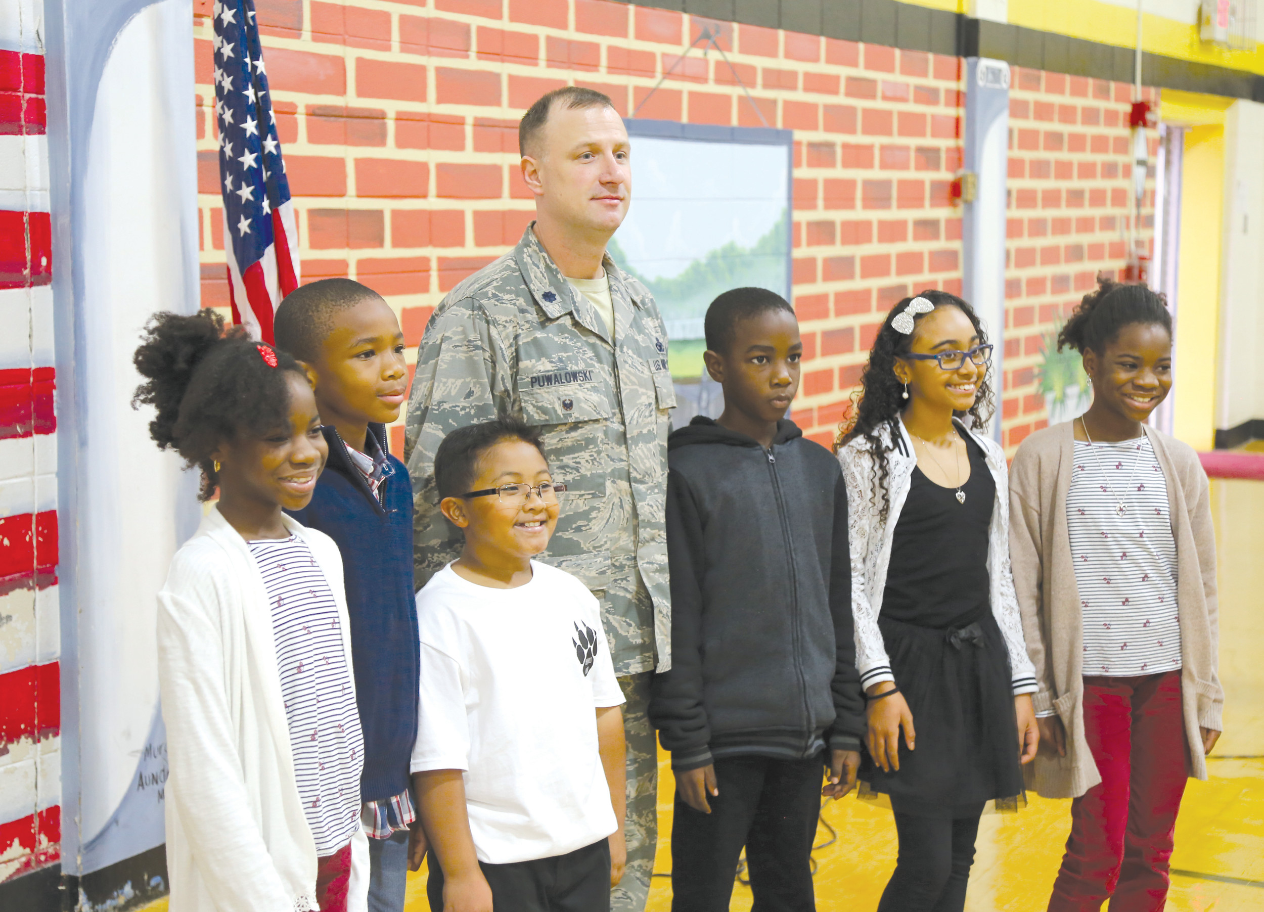 Shaw airman Lt. Col. Nathan Puwalowski poses with students from High Hills Elementary on Thursday during the school's Veterans Day program. Puwalowski was the keynote speaker for the event.