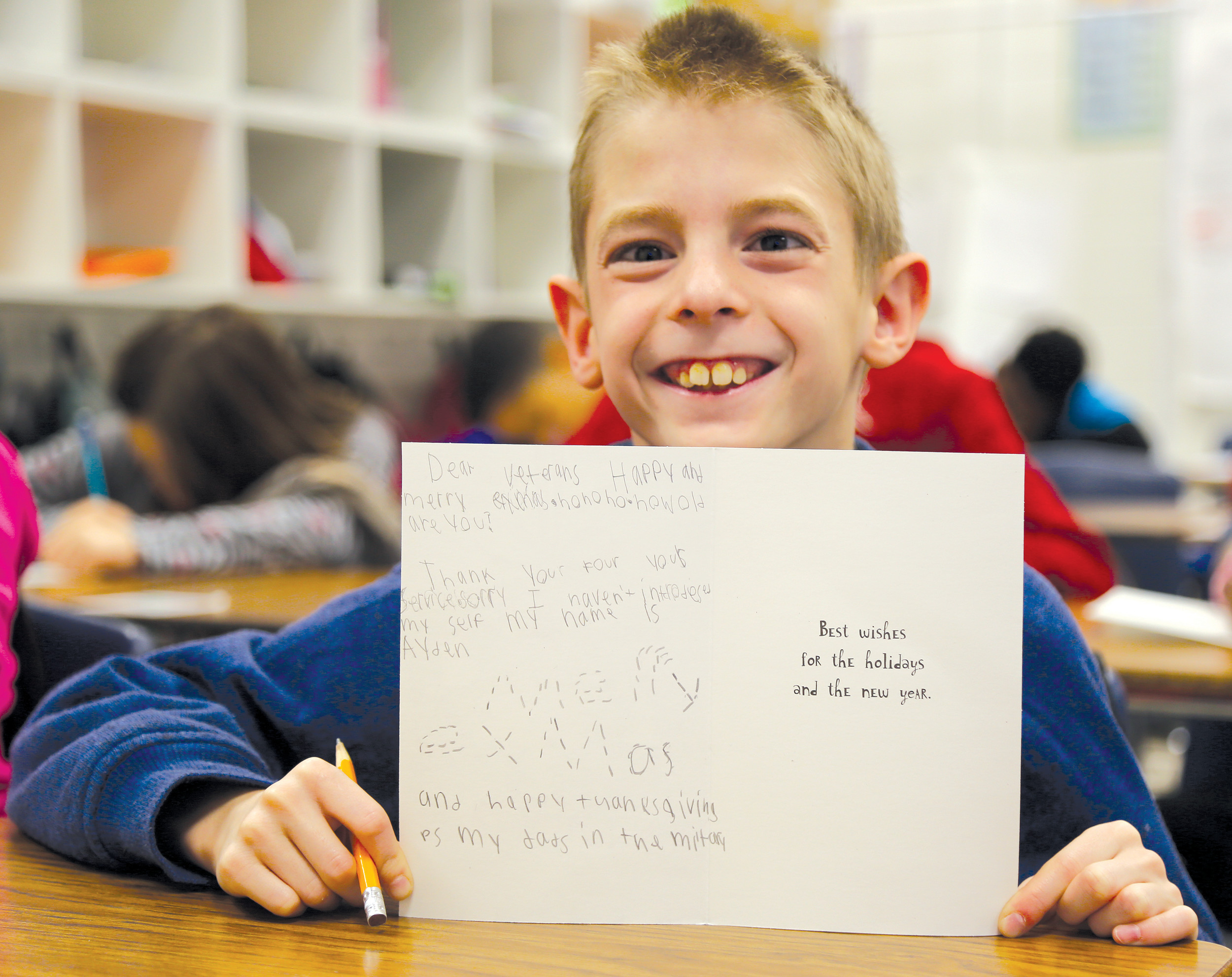 High Hills Elementary School fourth-grader Ayden Apato, 10, shows off a Christmas card he wrote to a veteran.