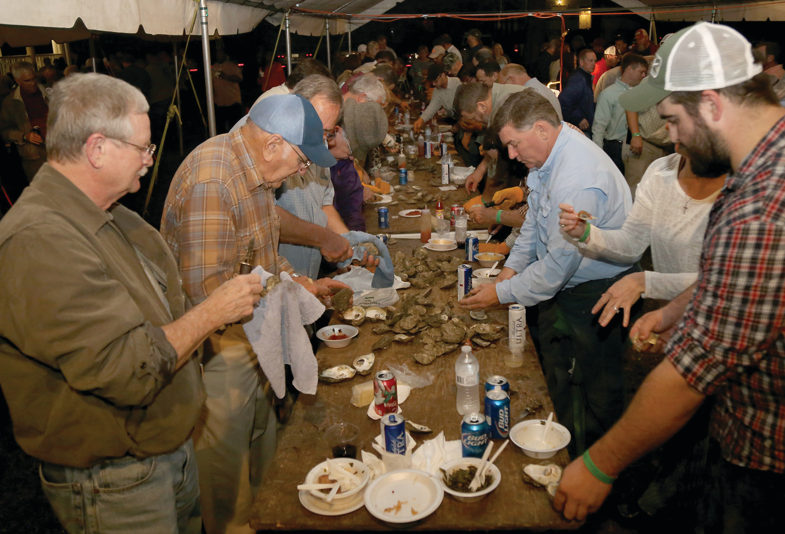 Sumter residents line long shucking tables at a past Sumter County Museum annual oyster roast.