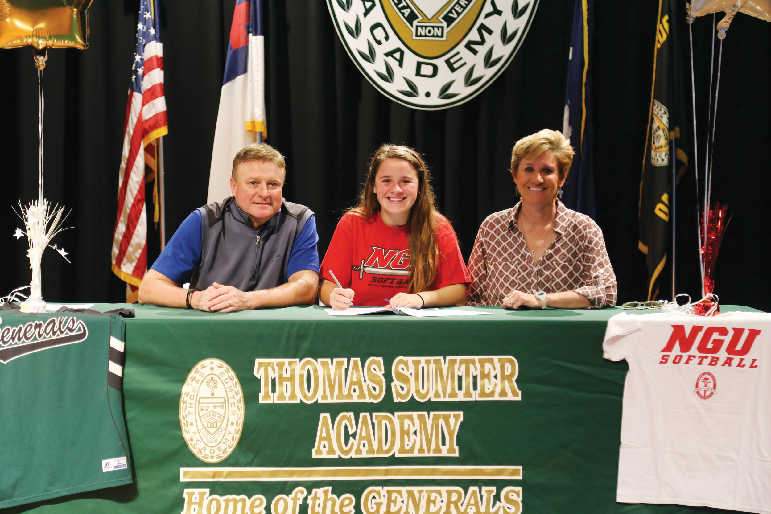 Thomas Sumter's Josie Reed is flanked by her parents as she signs a letter of intent to play softball at North Greenville University in Tigerville last week.